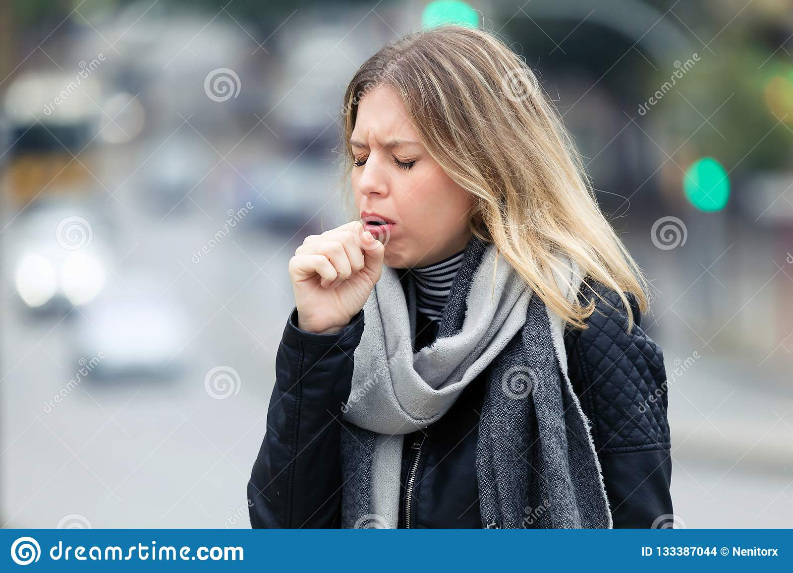 Illness young woman coughing in the street