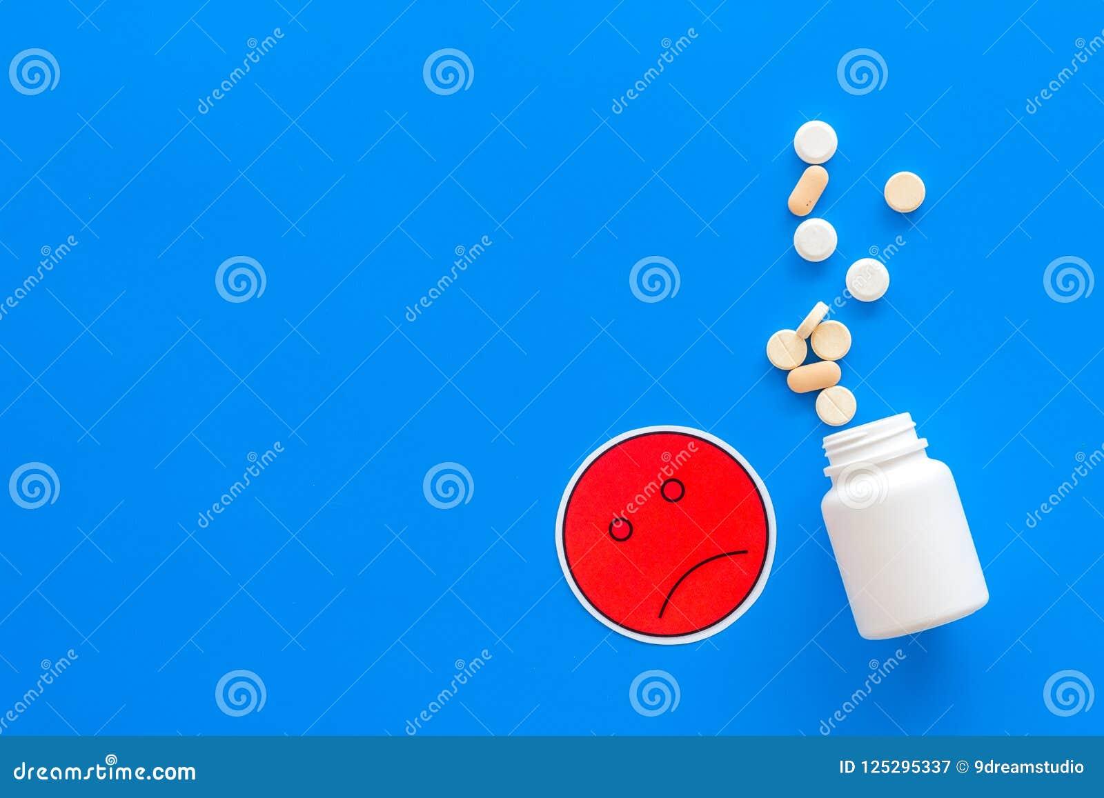 Illnesses Leka nabór Pigułki spada z słoju blisko smutnego twarzy emoji na błękitnej tło odgórnego widoku kopii przestrzeni