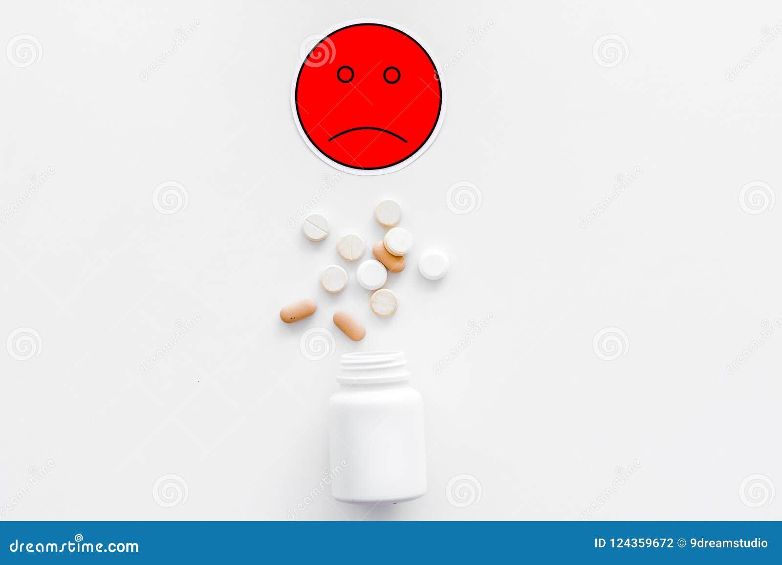 Illnesses Leka nabór Pigułki spada z słoju blisko smutnego twarzy emoji na białej tło odgórnego widoku kopii przestrzeni