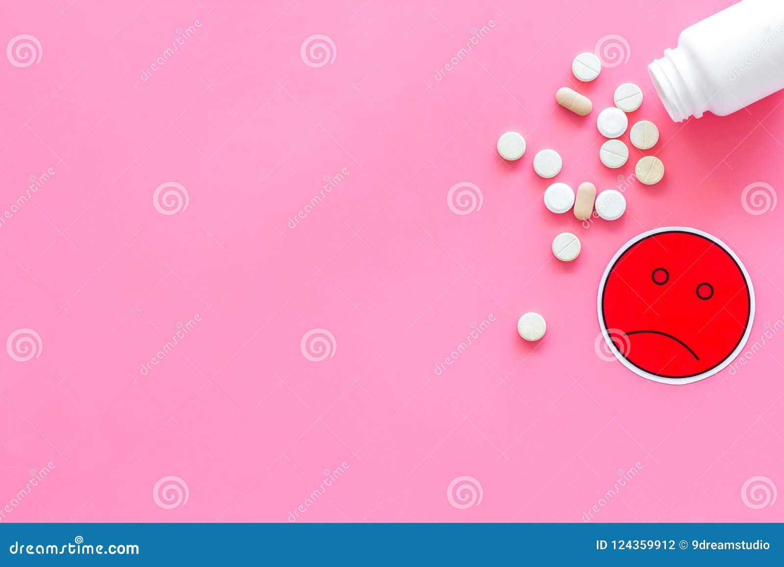 Illnesses Leka nabór Pigułki spada z słoju blisko smutnego twarzy emoji na różowej tło odgórnego widoku kopii przestrzeni
