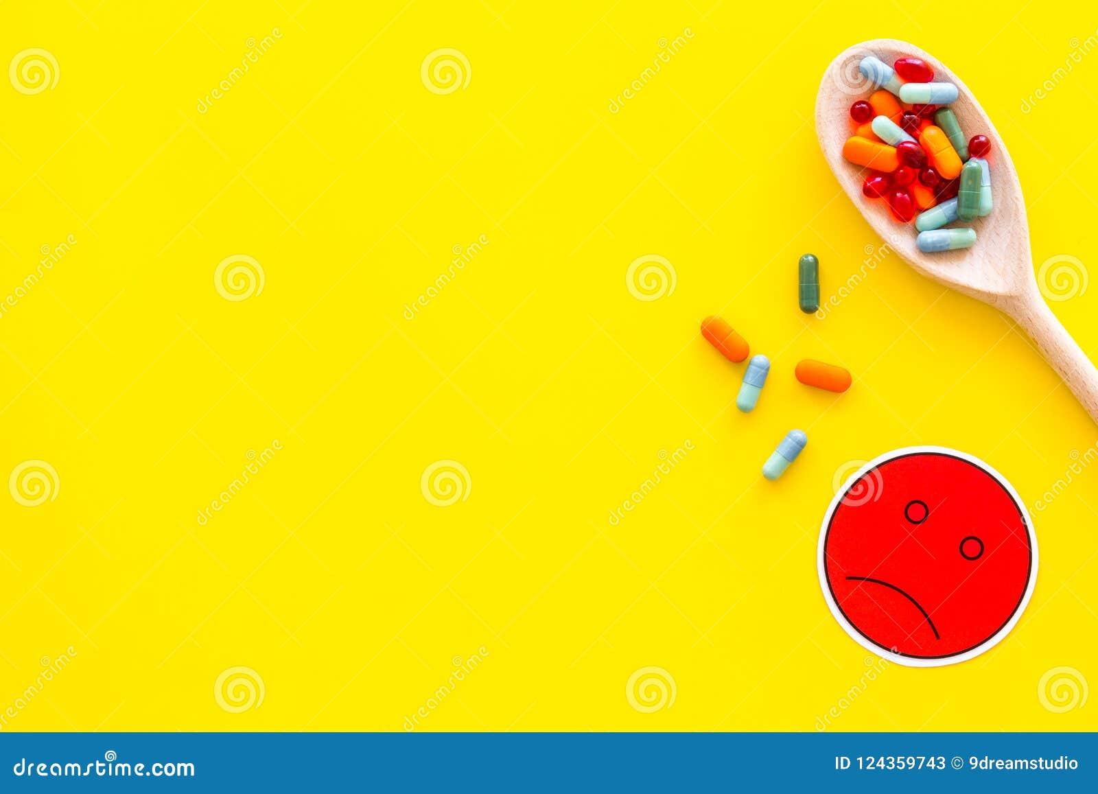 Illnesses Leka nabór Pigułki w łyżkowym pobliskim smutnym twarzy emoji na żółtej tło odgórnego widoku kopii przestrzeni