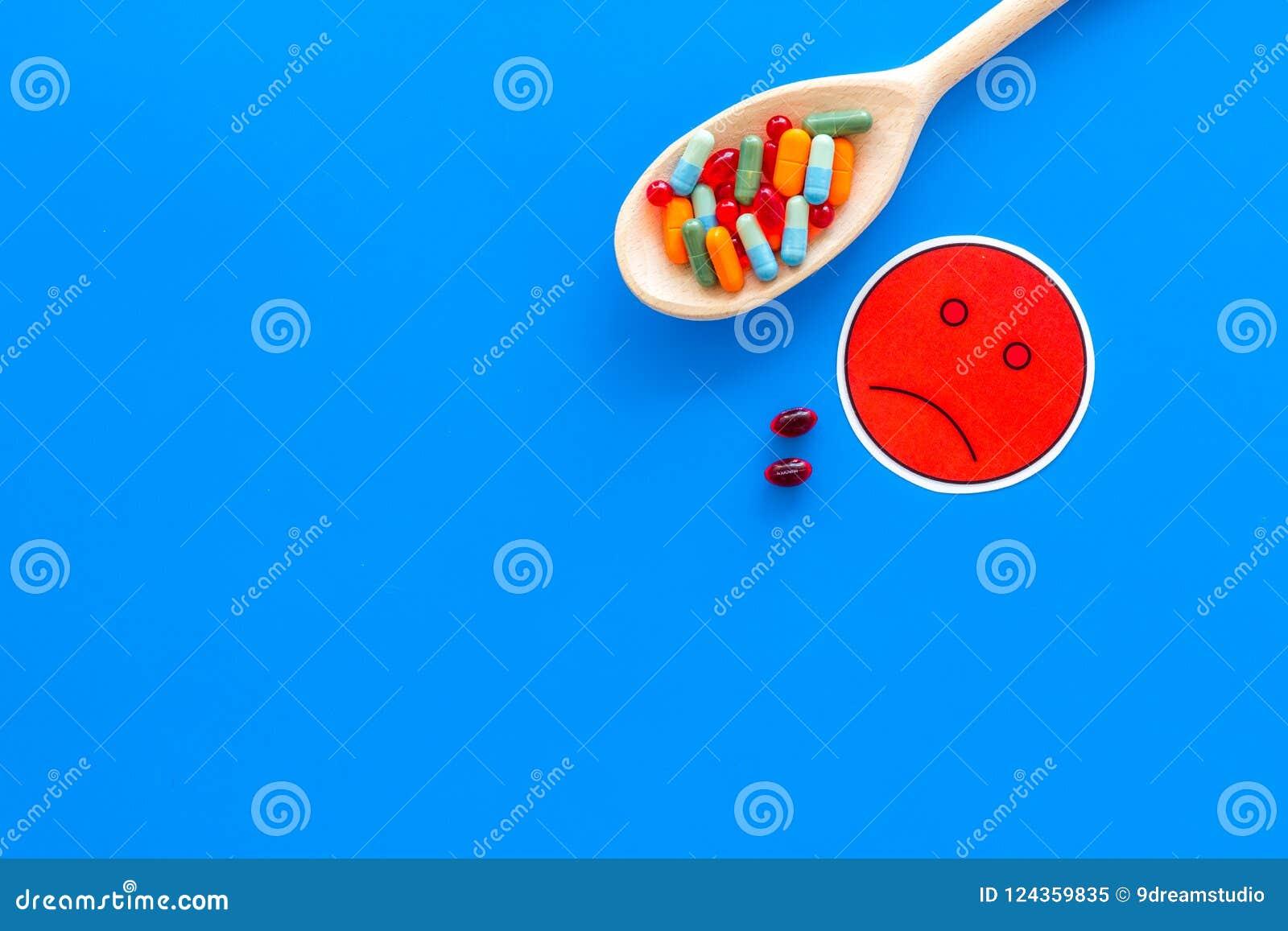 Illnesses Leka nabór Pigułki w łyżkowym pobliskim smutnym twarzy emoji na błękitnej tło odgórnego widoku kopii przestrzeni