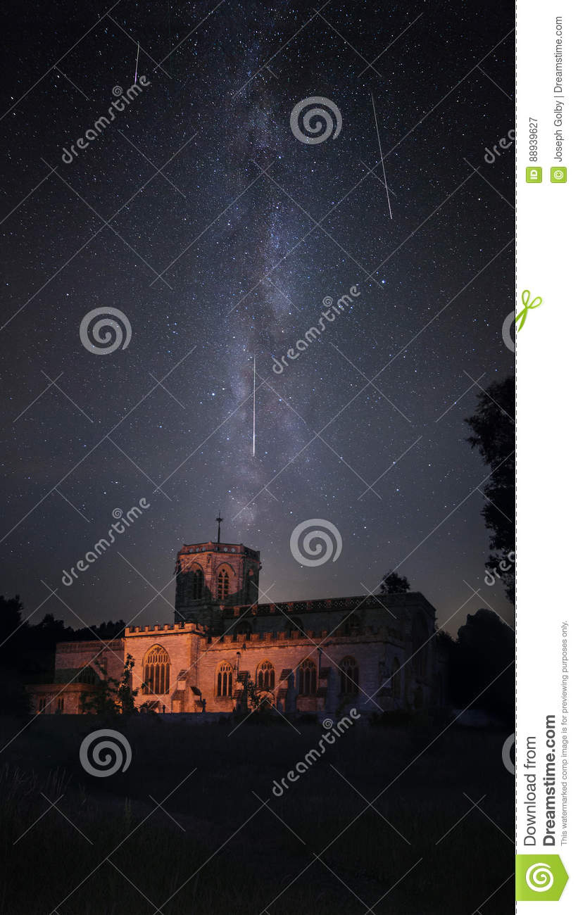 Illuminated church with milky way night sky during Perseid meteor shower