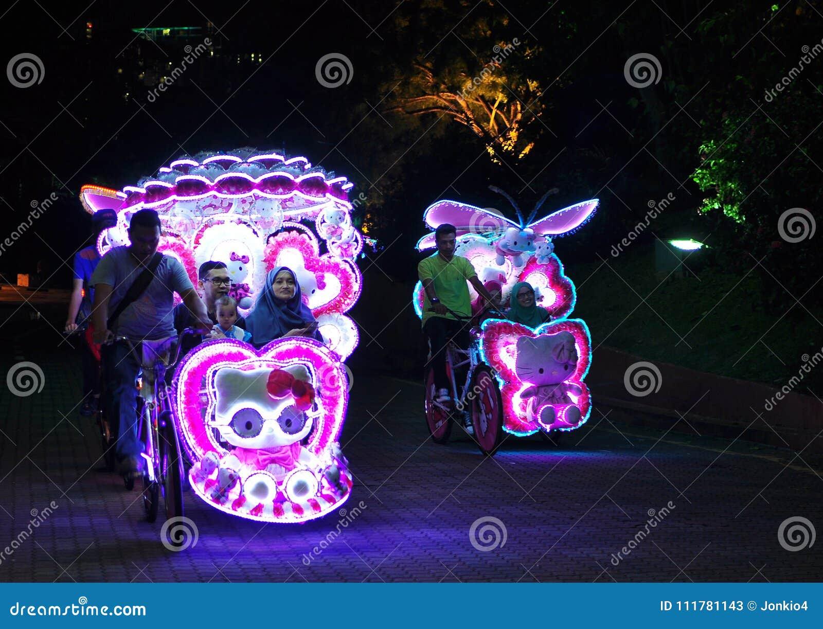 Illuminated decorated trishaw with soft toys at night in Malacca, Malaysia
