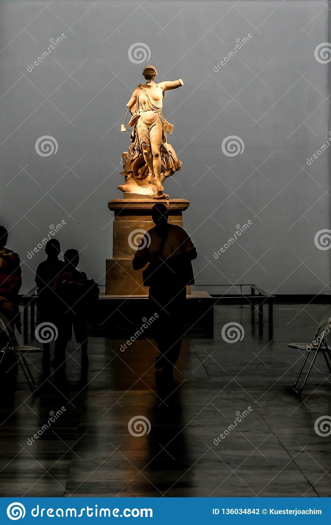 Illuminated hellenic statue of a woman in a museum with visitors