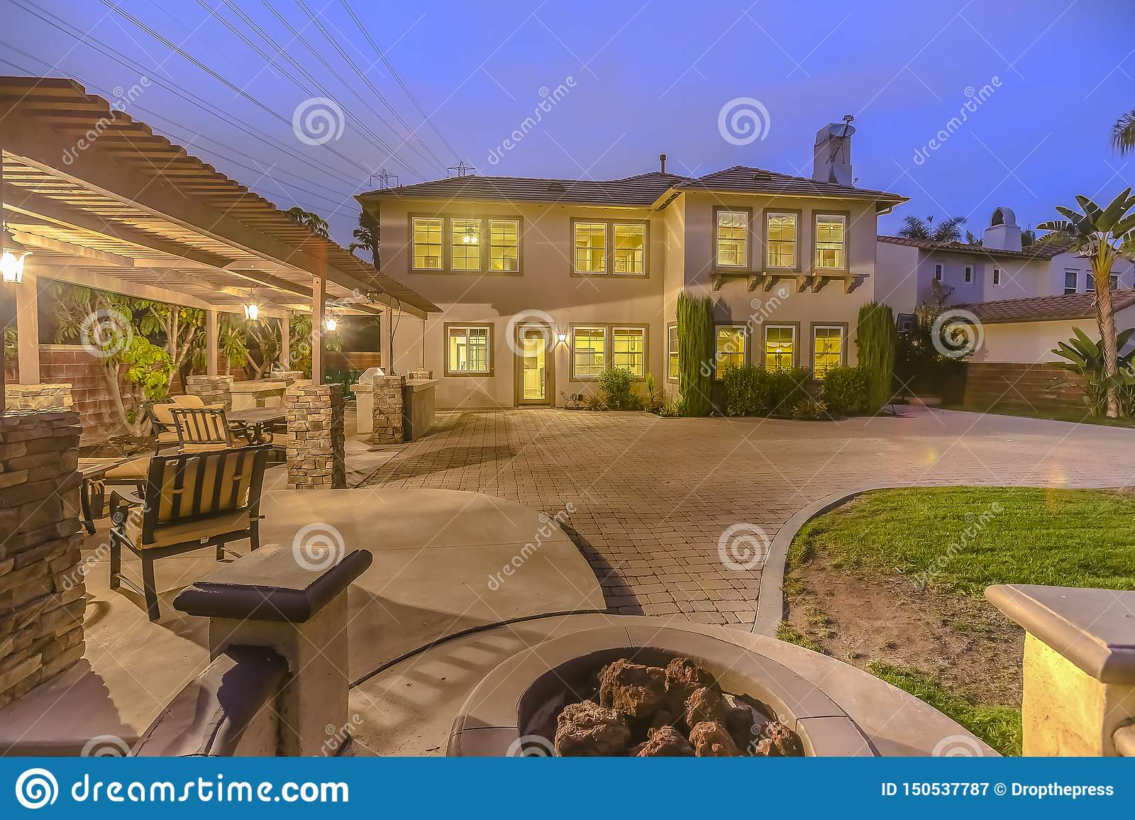 Illuminated House With A Patio Accomodating An Outdoor Dining Area And Fire Pit Stock Image Image Of Area Trees 150537787