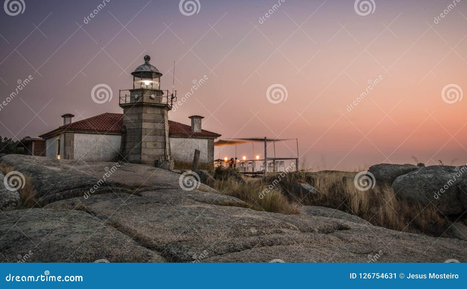 Illuminated lighthouse over the sea and the coast of Galicia