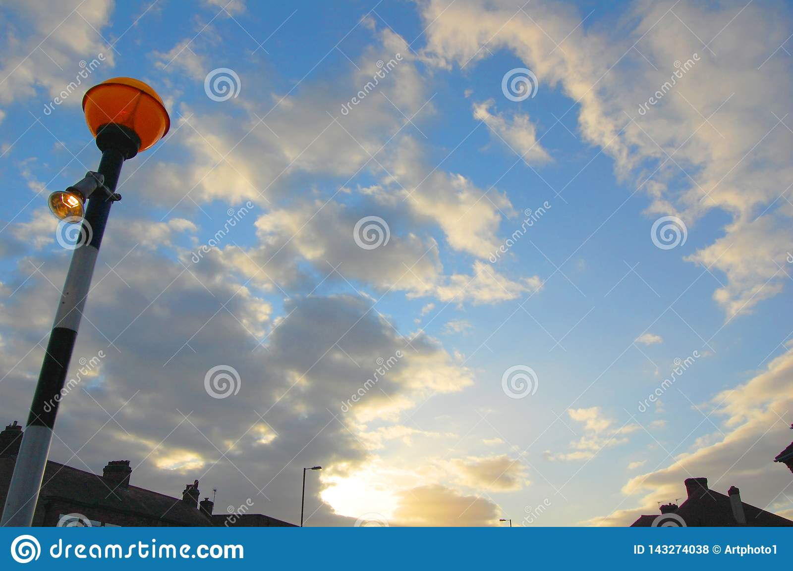 Illuminated orange safety crossing beacon set against peaceful evening light blue and fluffy white clouds