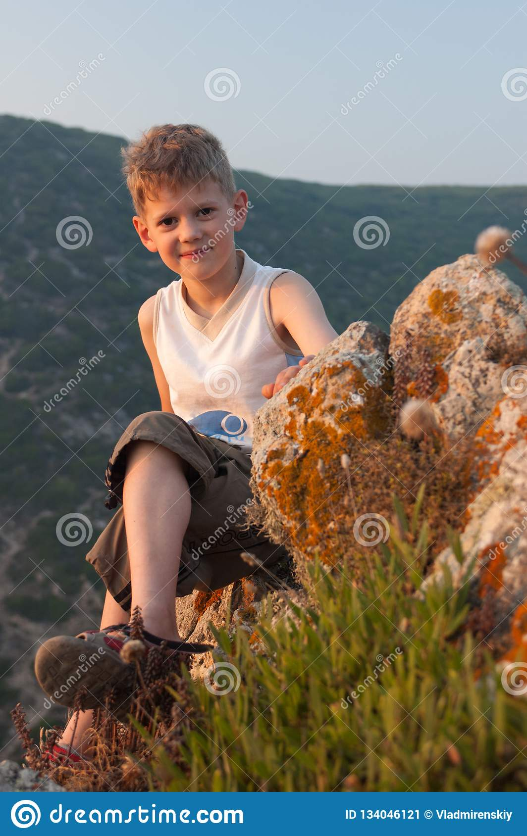 Illuminated by the warm light of the sunset sun, the boy sits on the edge of a cliff