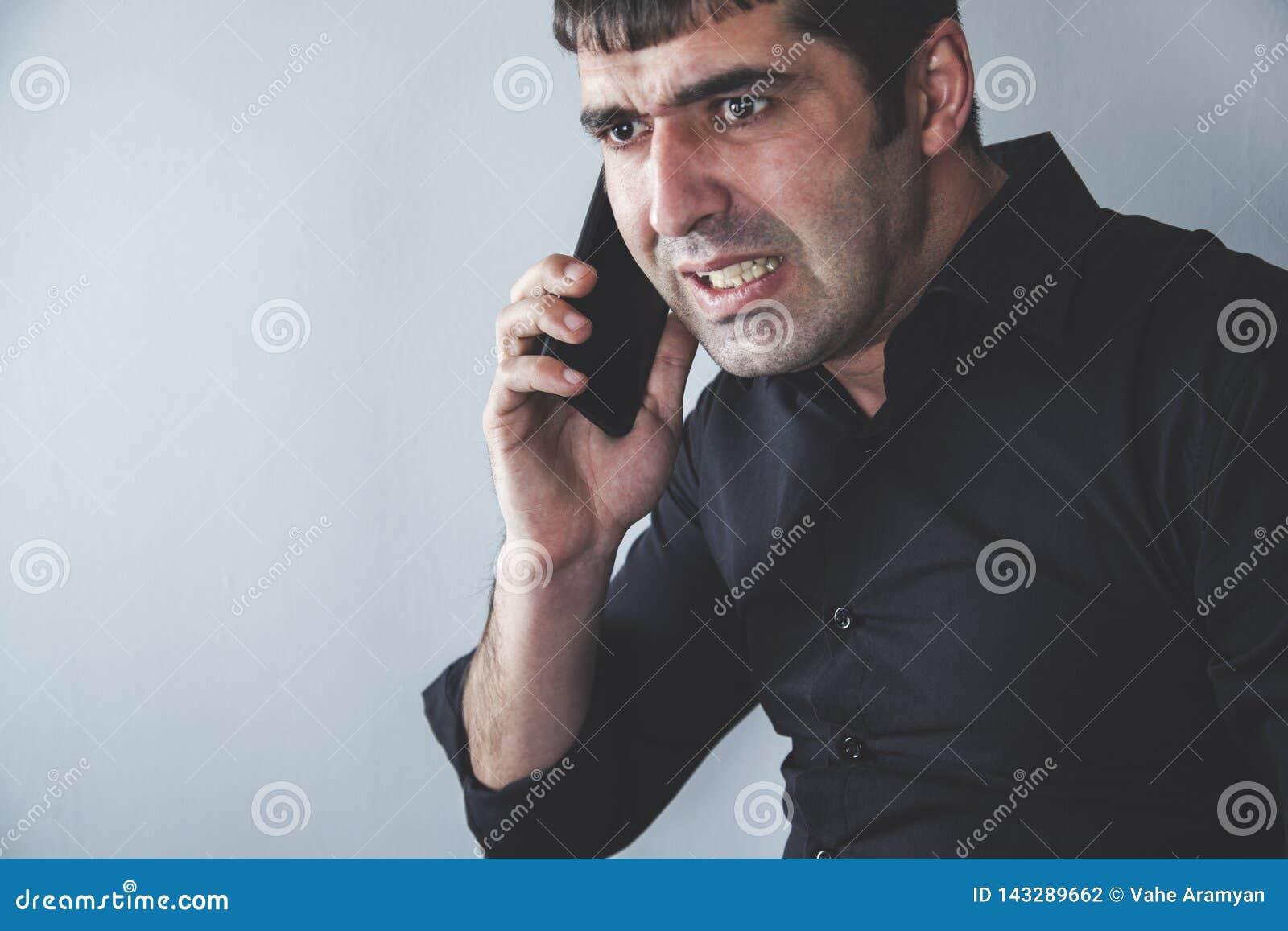 Ilsken man som talar i telefon