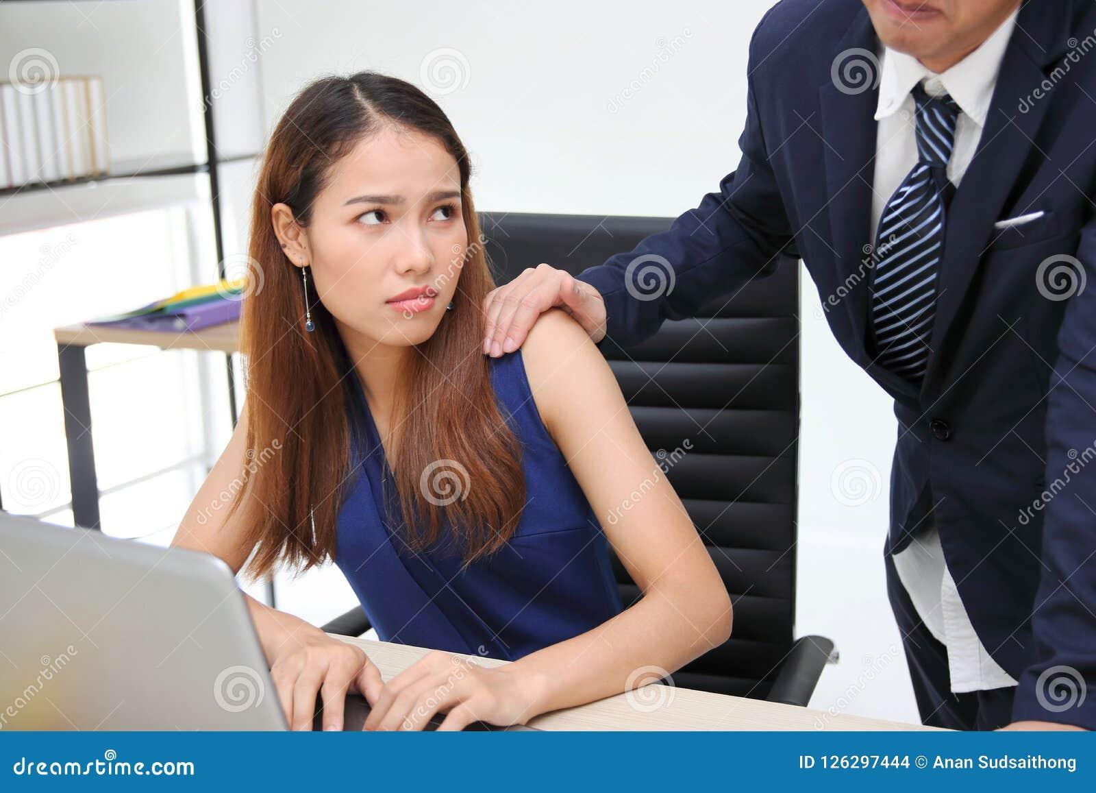 Ilsken olycklig asiatisk sekreterarekvinna som ser framstickandet för hand` som s trycker på hennes skuldra i arbetsplats sexuell