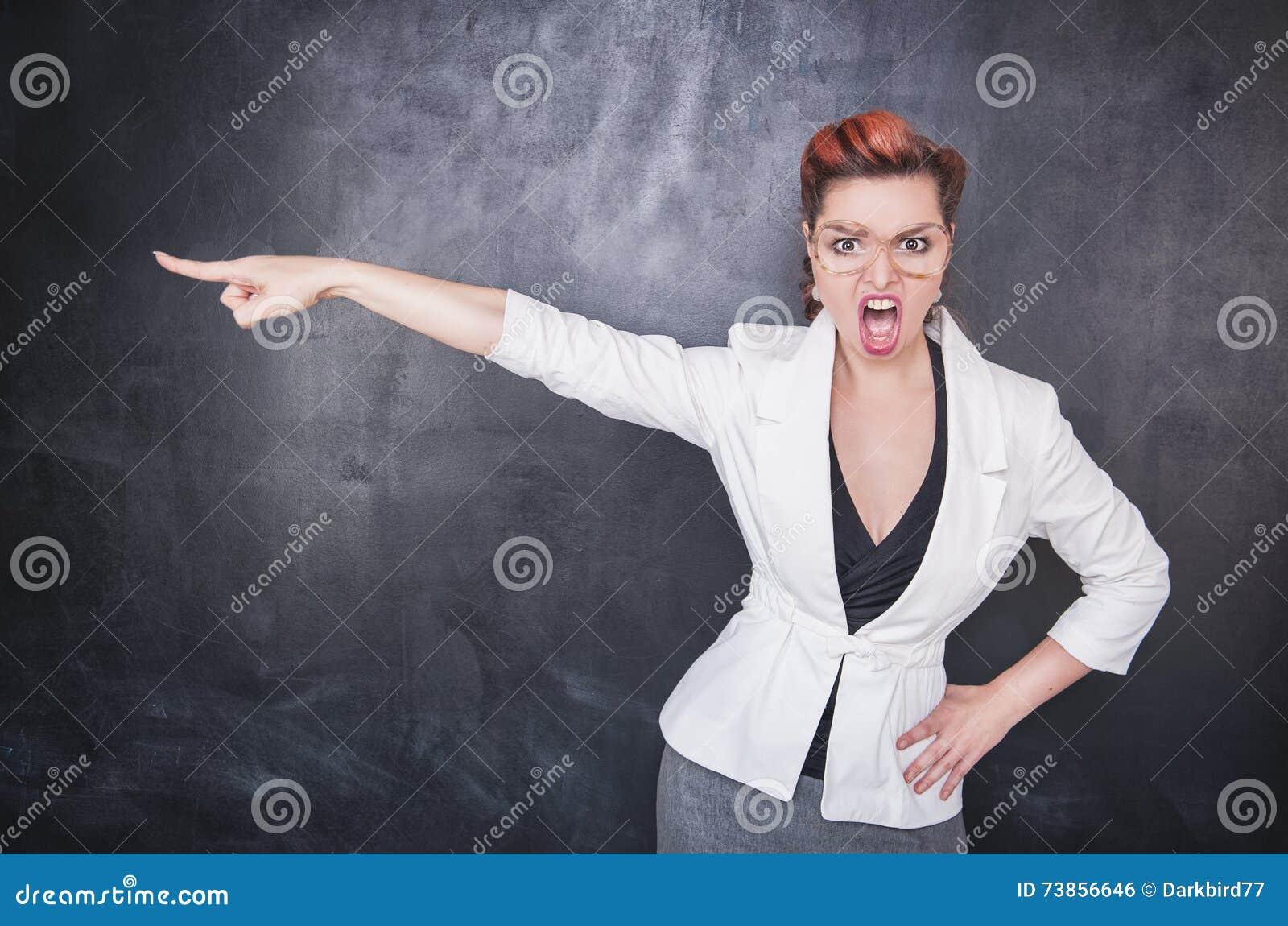 Ilsken skrikig lärare som pekar ut på svart tavlabakgrund