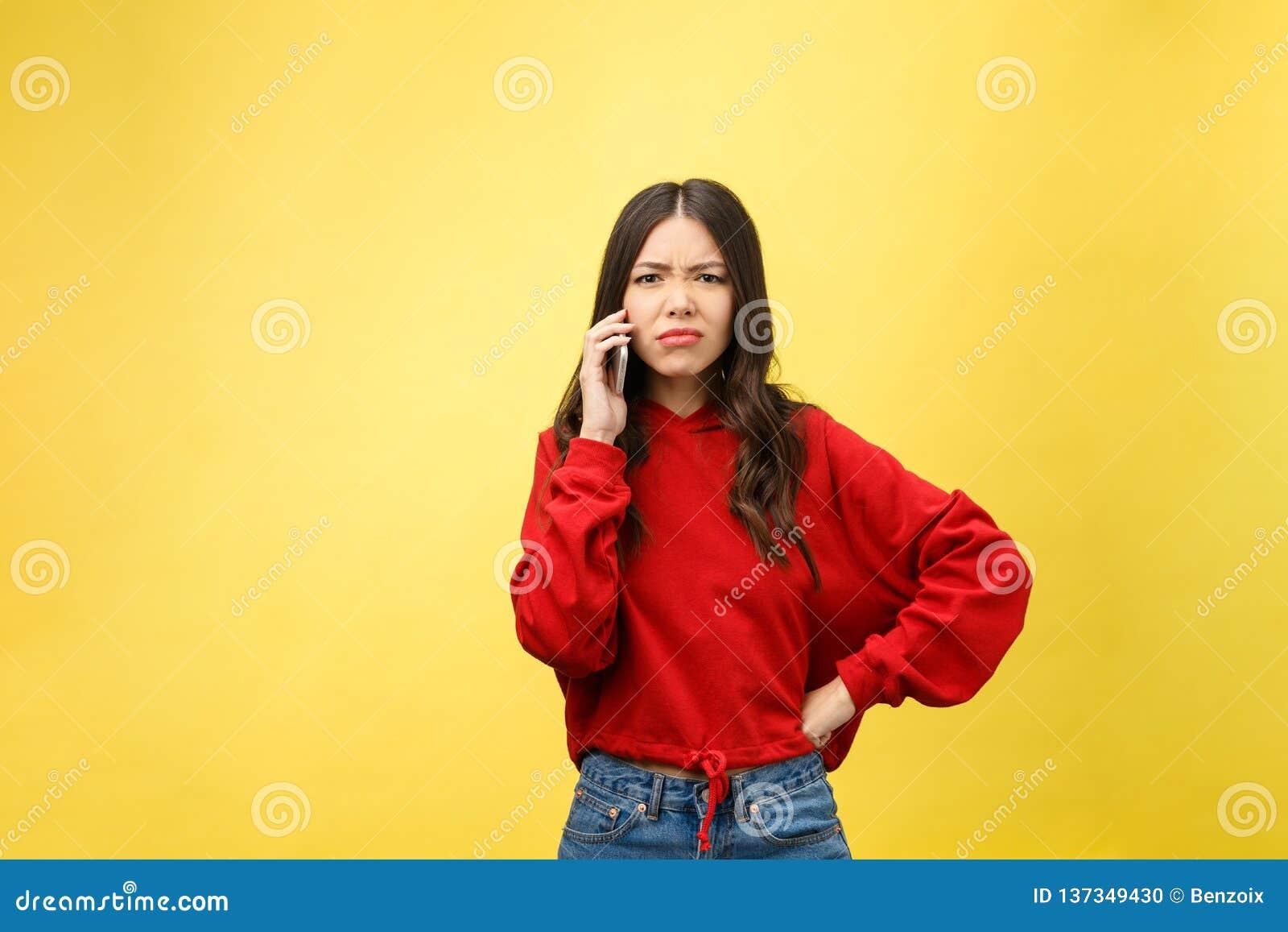 Ilsken ung asiatisk kvinna för stående att svika på mobiltelefonen, medan stå över gul bakgrund