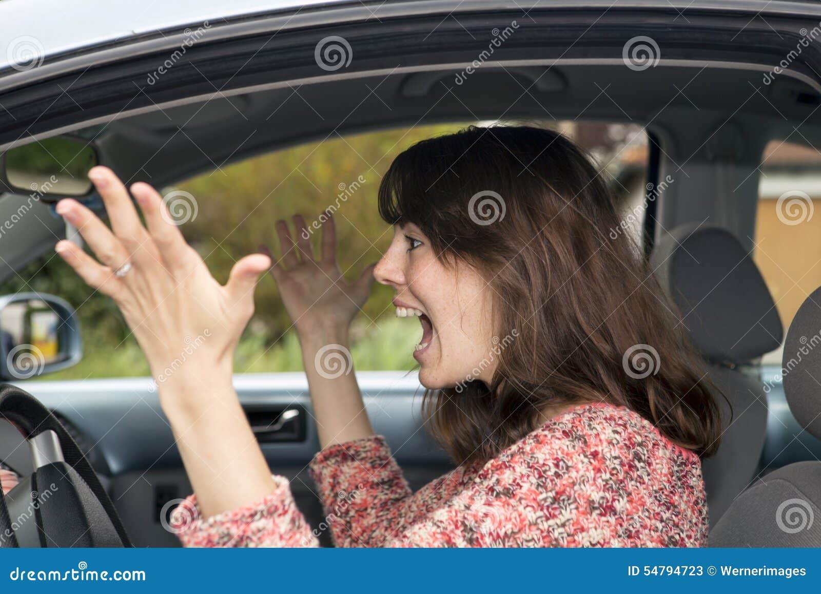 Ilsken ung kvinna som kör i bil
