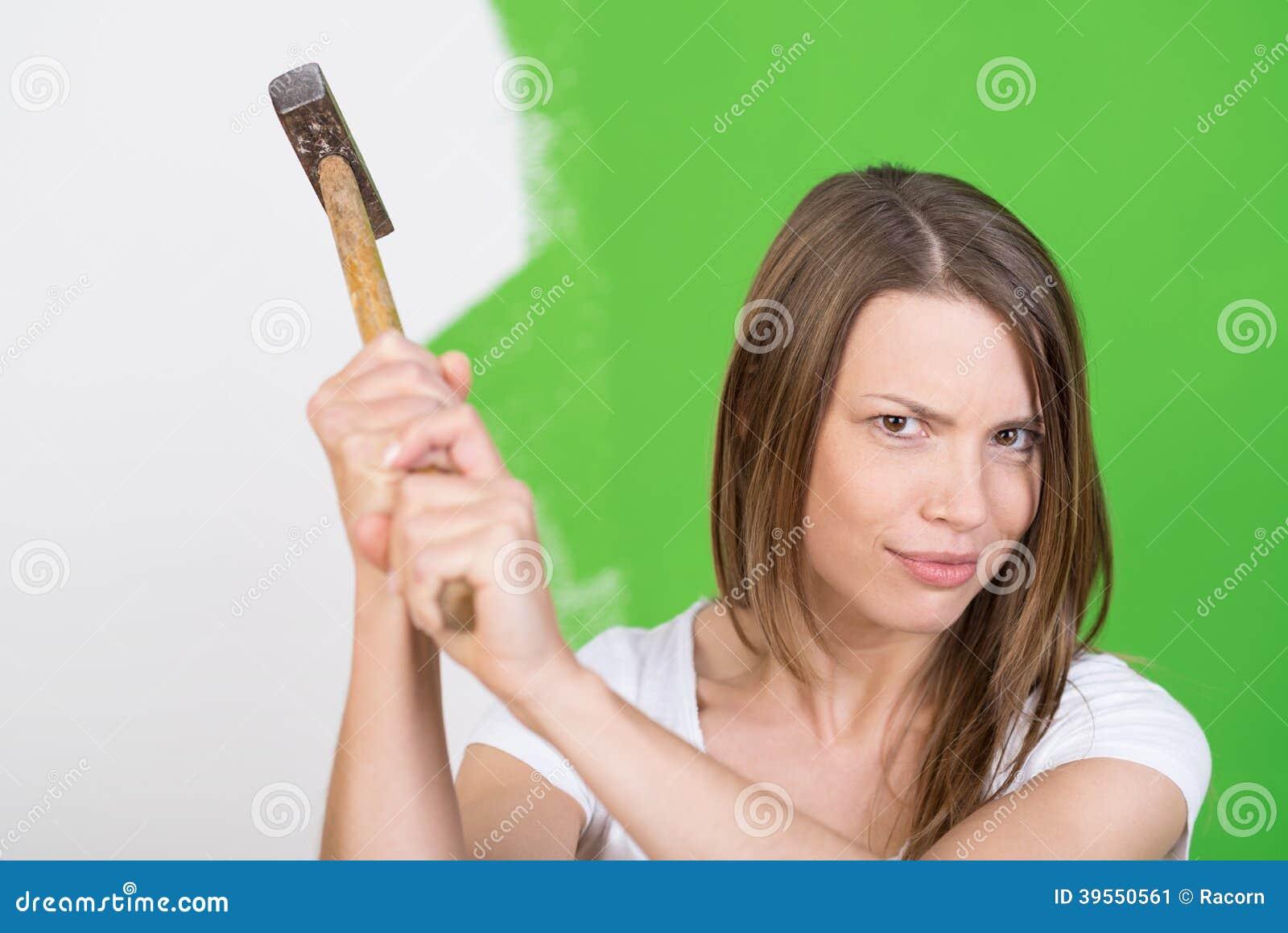 Ilsken ung kvinna som lyfter en hammare i luften