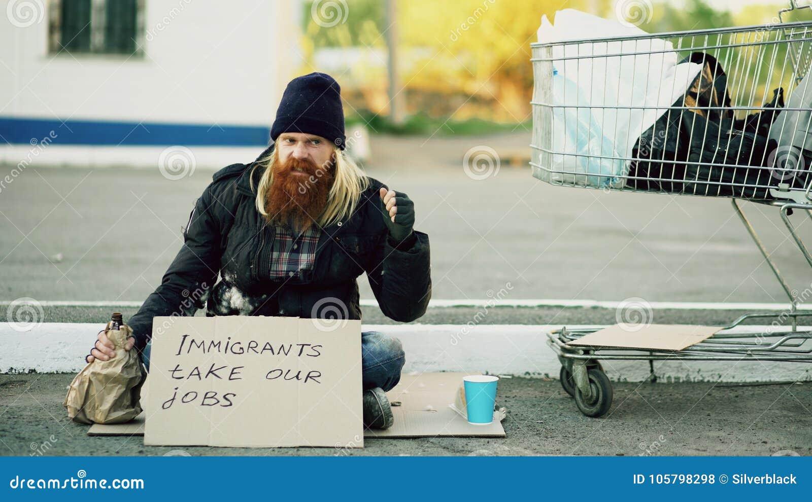 Ilsken uppriven ung hemlös man med papp som sitter nära shoppingvagnen och drinkalkohol på den kalla dagen på grund av