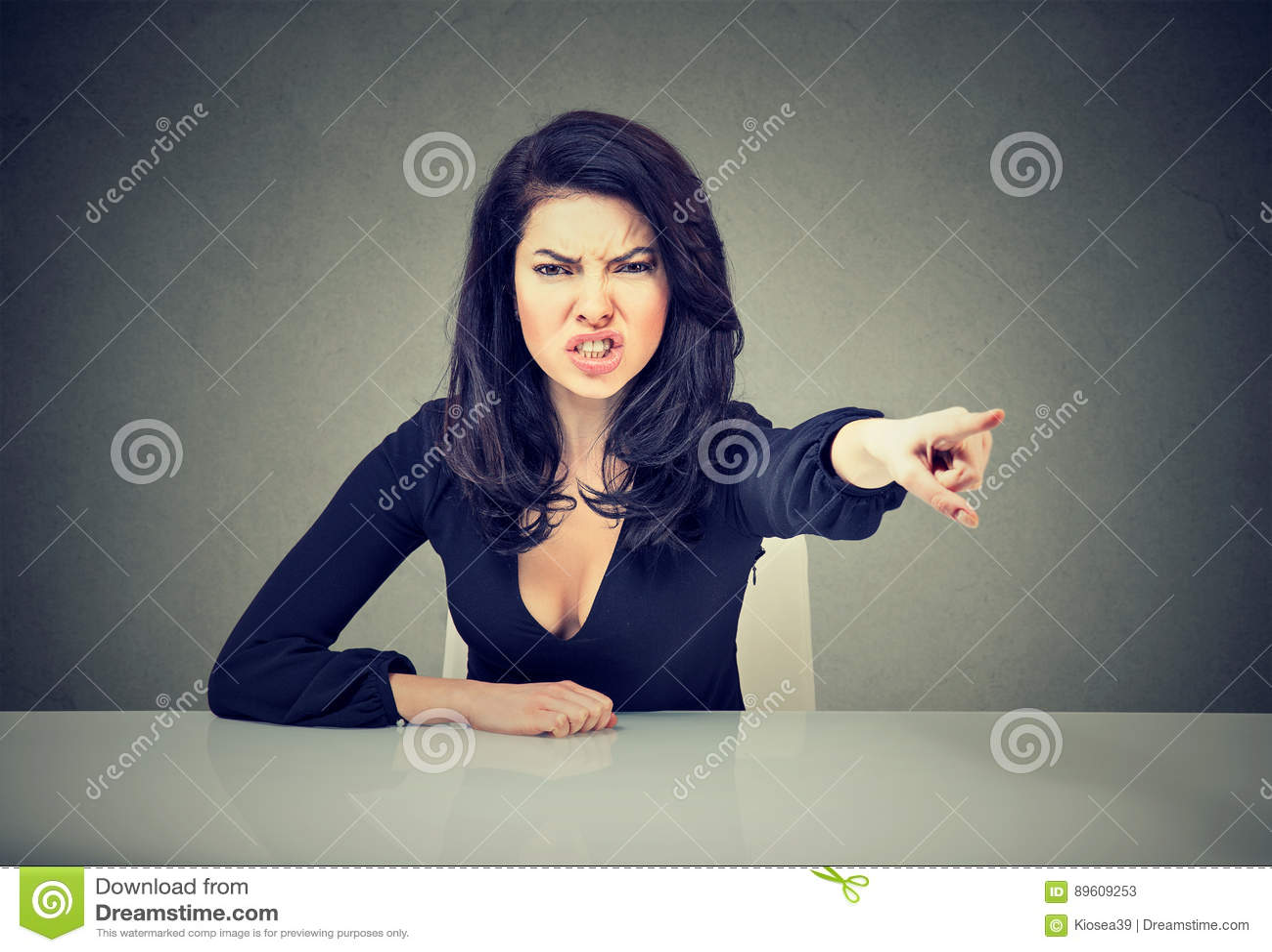 Ilsket sammanträde för affärskvinna på hennes skrivbord och skrika att peka med fingret som ska fås ut