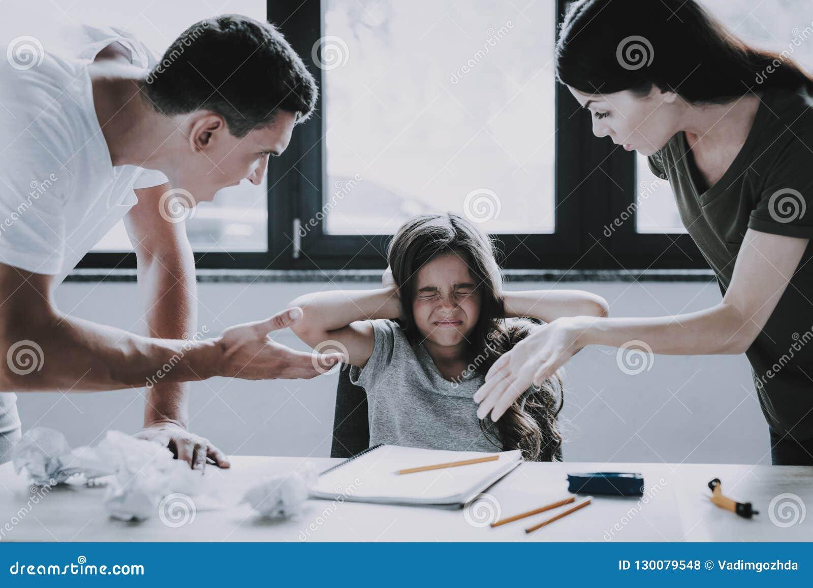 Ilskna förälderskrän på flickan medan göra för läxa