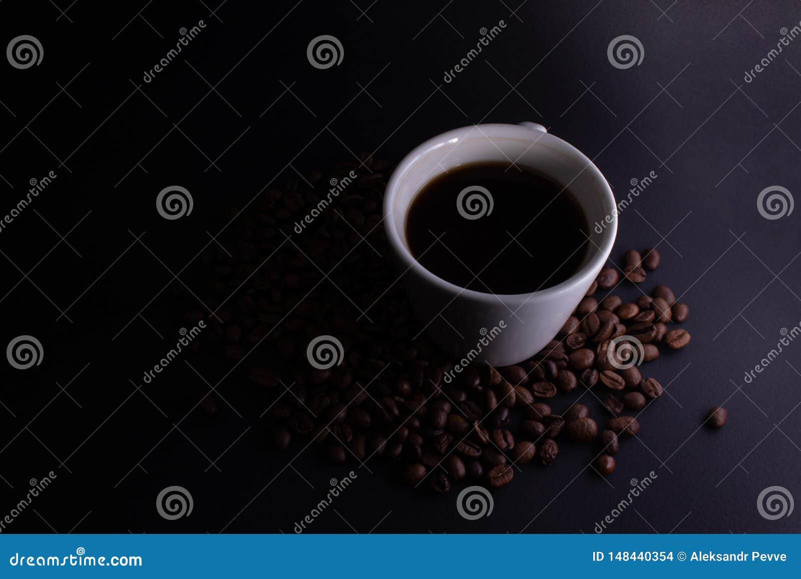 Iluminação do inclinação de um copo com café forte preto em um fundo escuro com os feijões de café espalhados