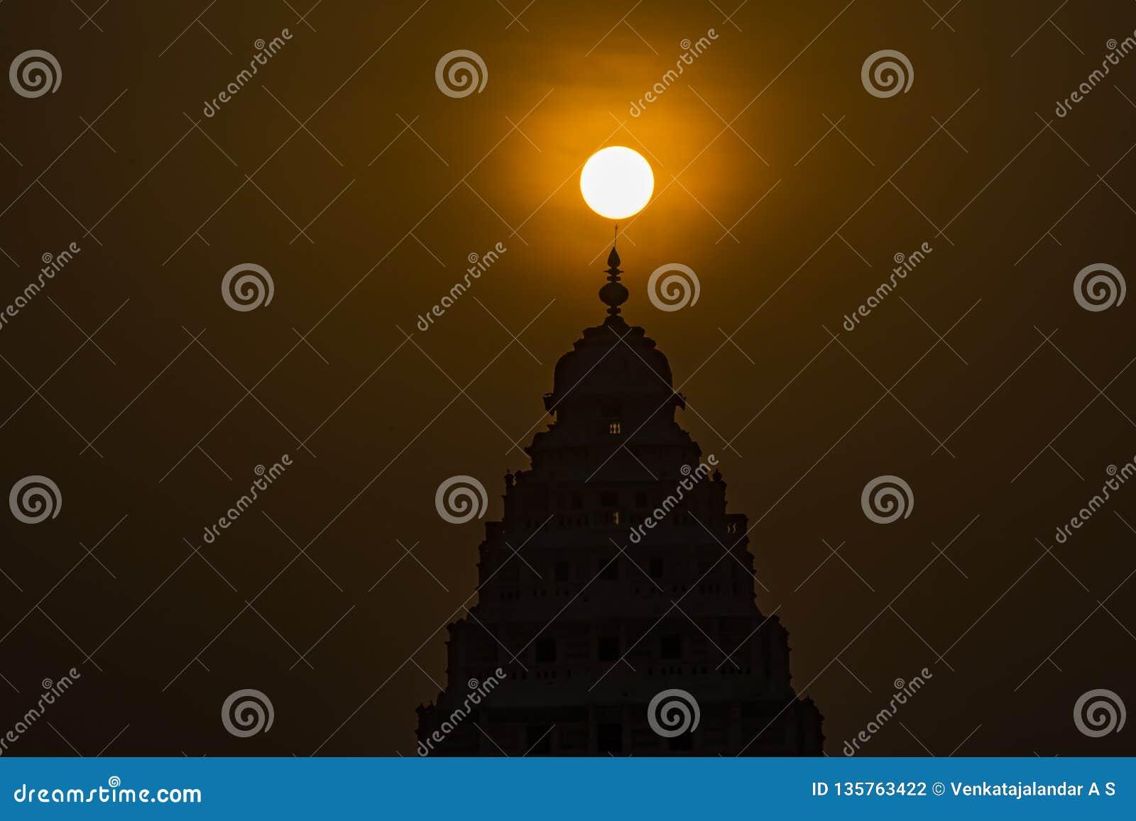 Iluminação: Nascer do sol acima da parte superior de um templo hindu