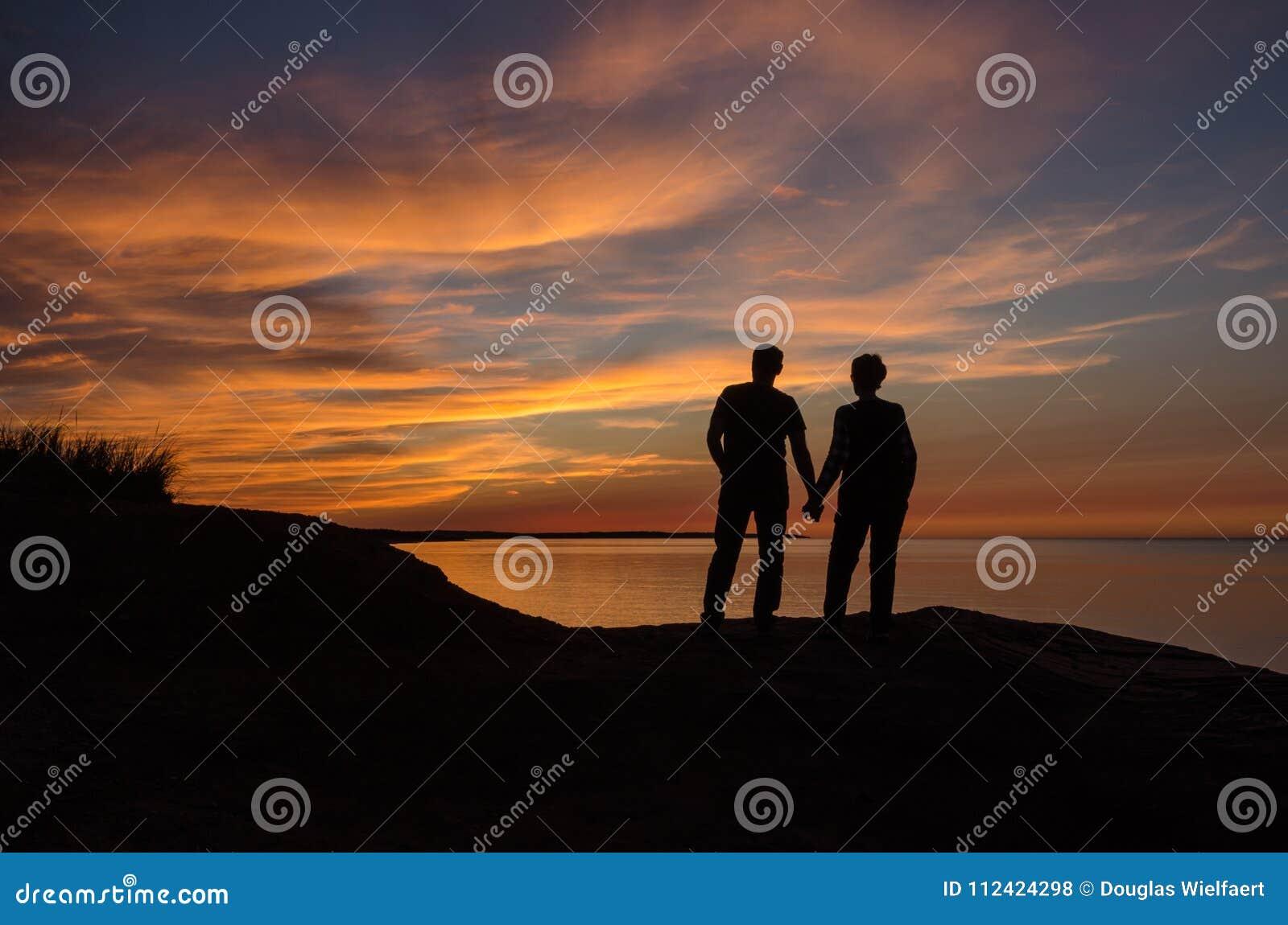 Iluminação traseira dos pares que guardam agains por do sol vermelho das mãos, raios de sol