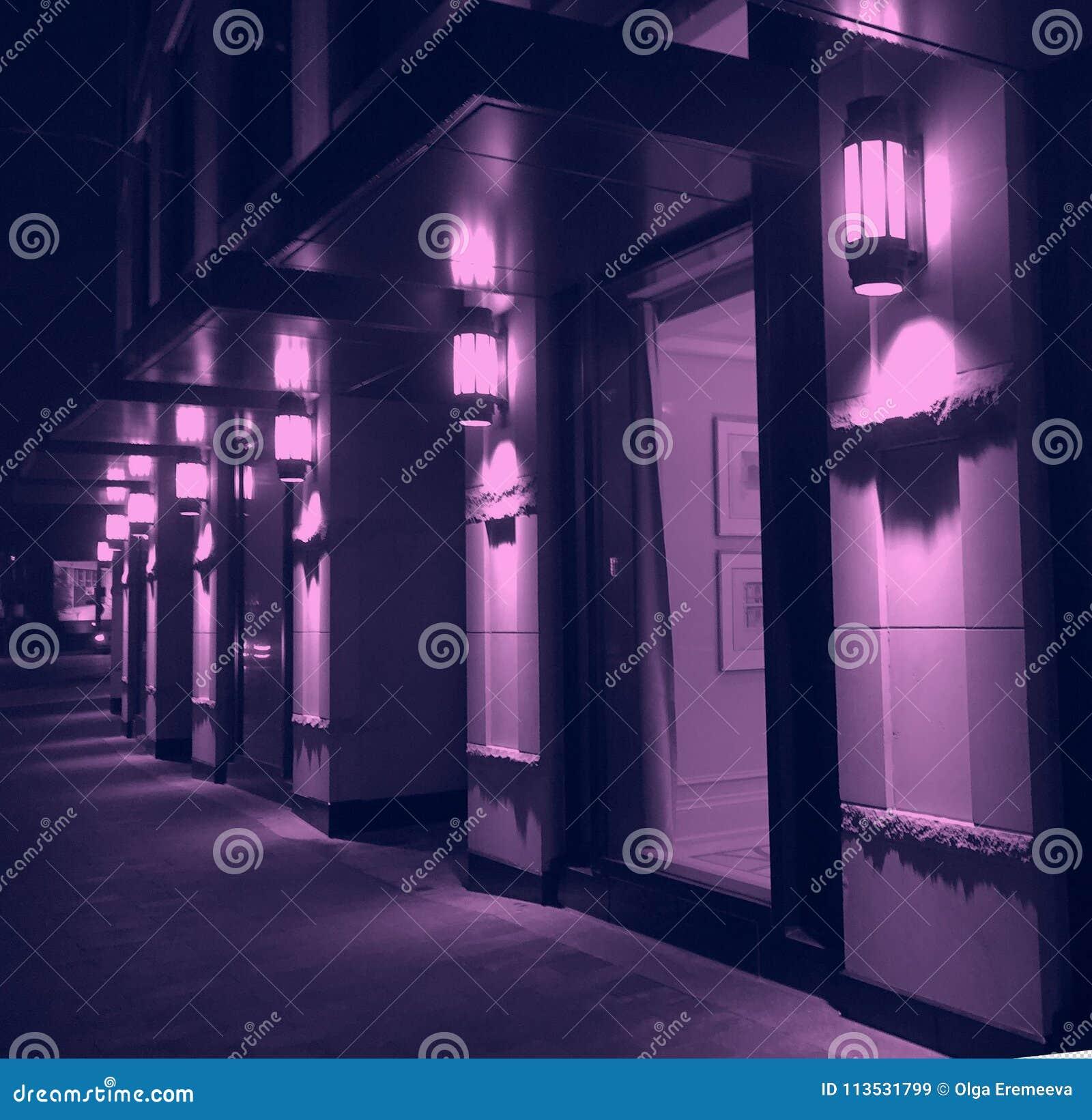 Iluminación violeta de la noche de la fachada moderna del edificio de la ciudad
