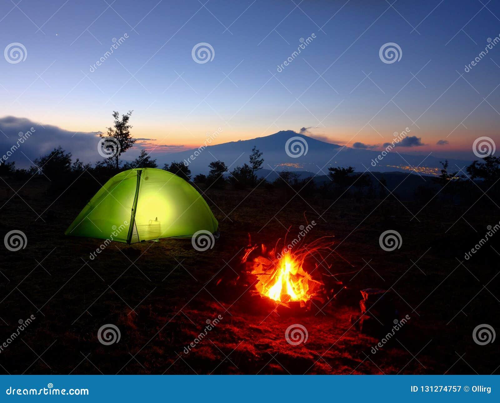 Iluminando a barraca, a fogueira e a Volcano Etna At Dawn, Sicília