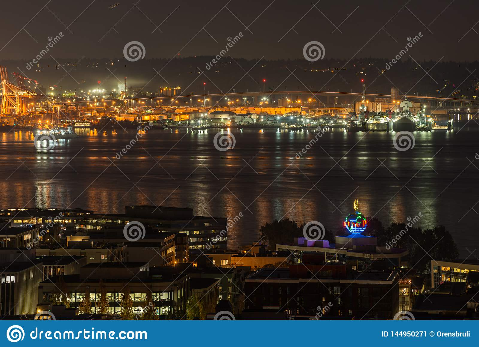 Iluminate оранжевых светов порт залива Сиэтл и Elliott вечером