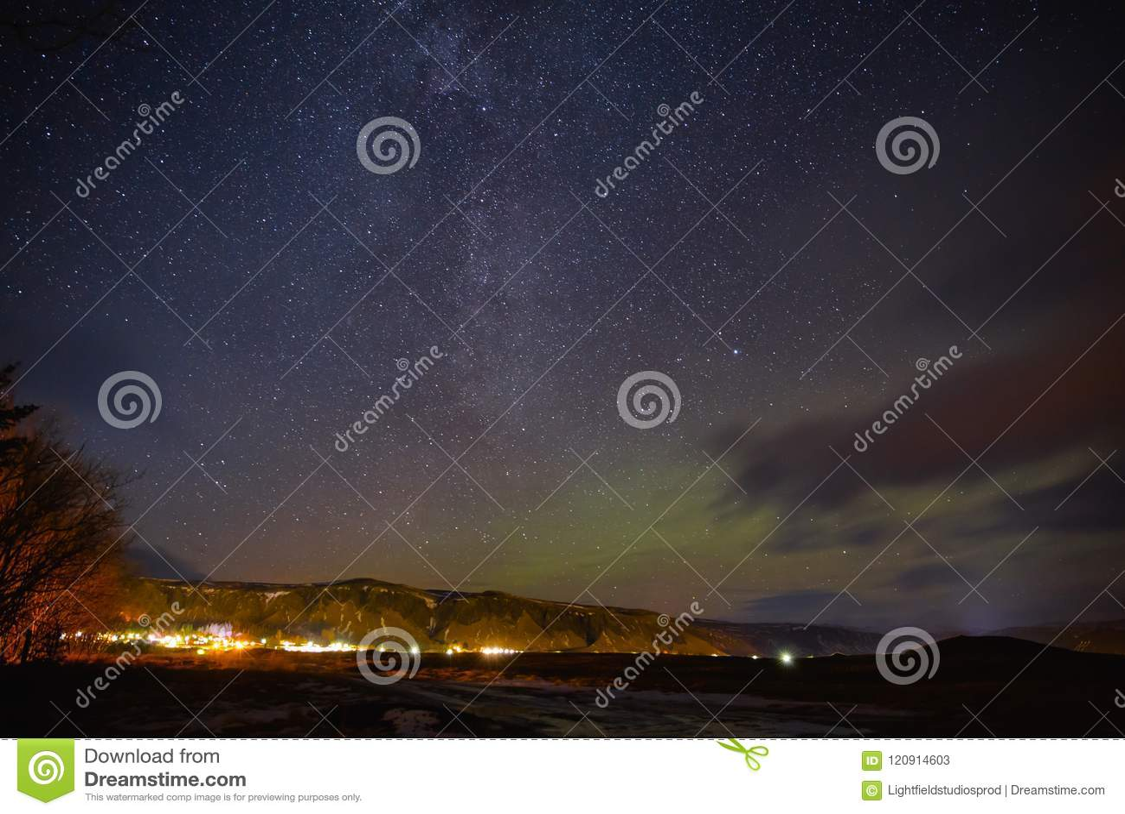 Iluminujący budynki i piękny gwiaździsty niebo z północnymi światłami