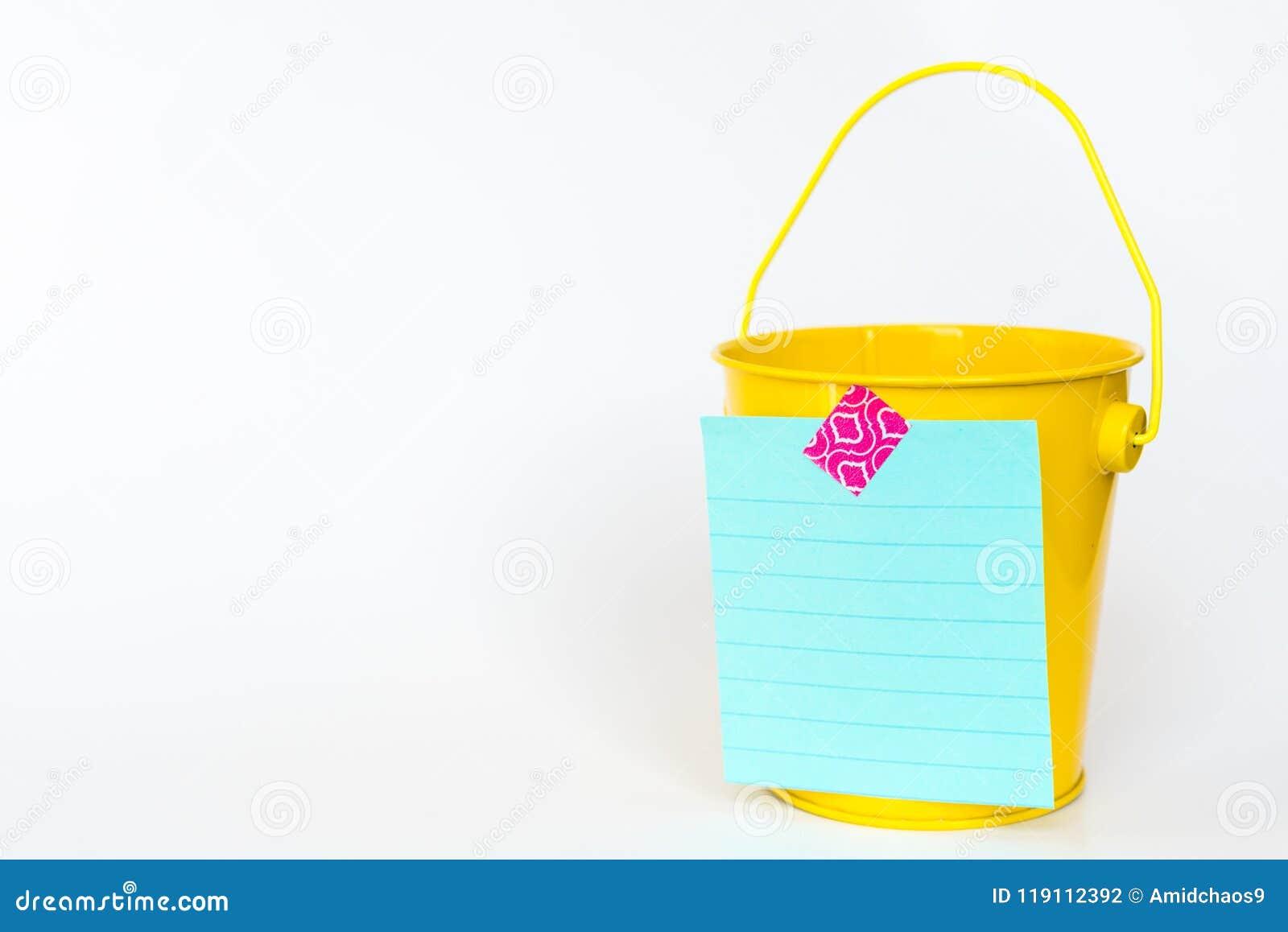 Ilustracja wiadro listy pojęcie z żółtego metalu wiadrem i lista nagrywająca stać na czele przeciw białemu tłu