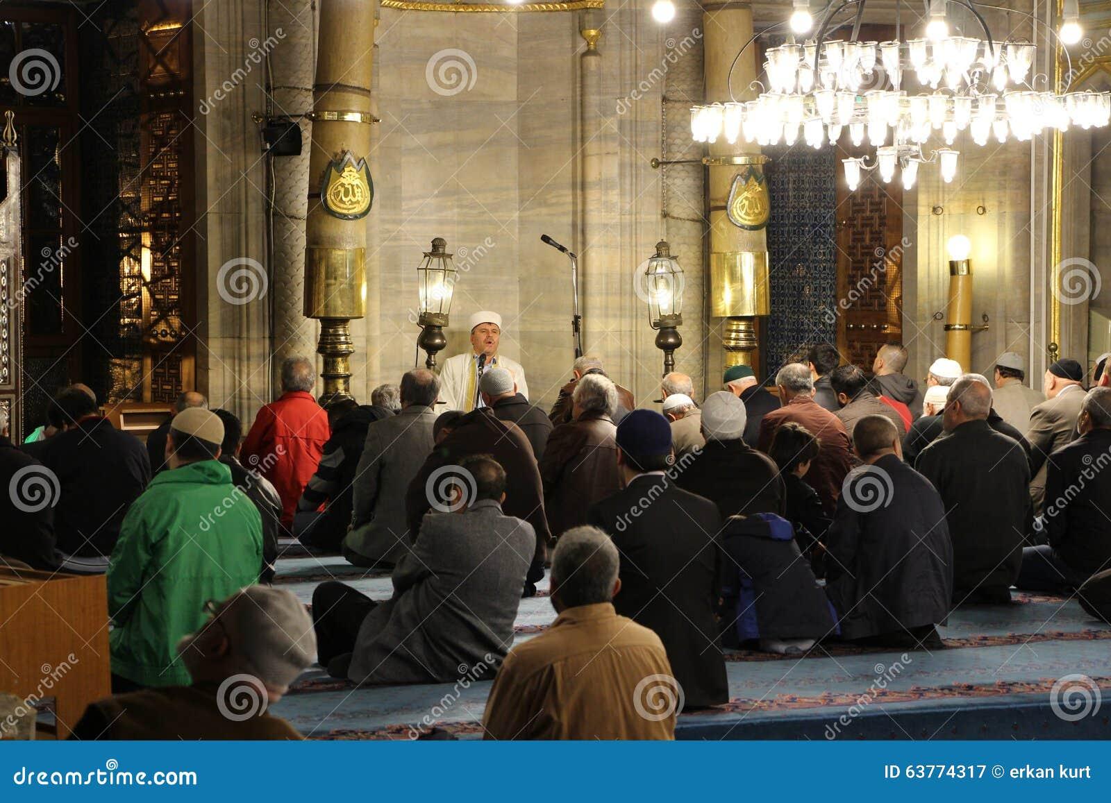 Imã, lendo o Alcorão na mesquita nova Istambul