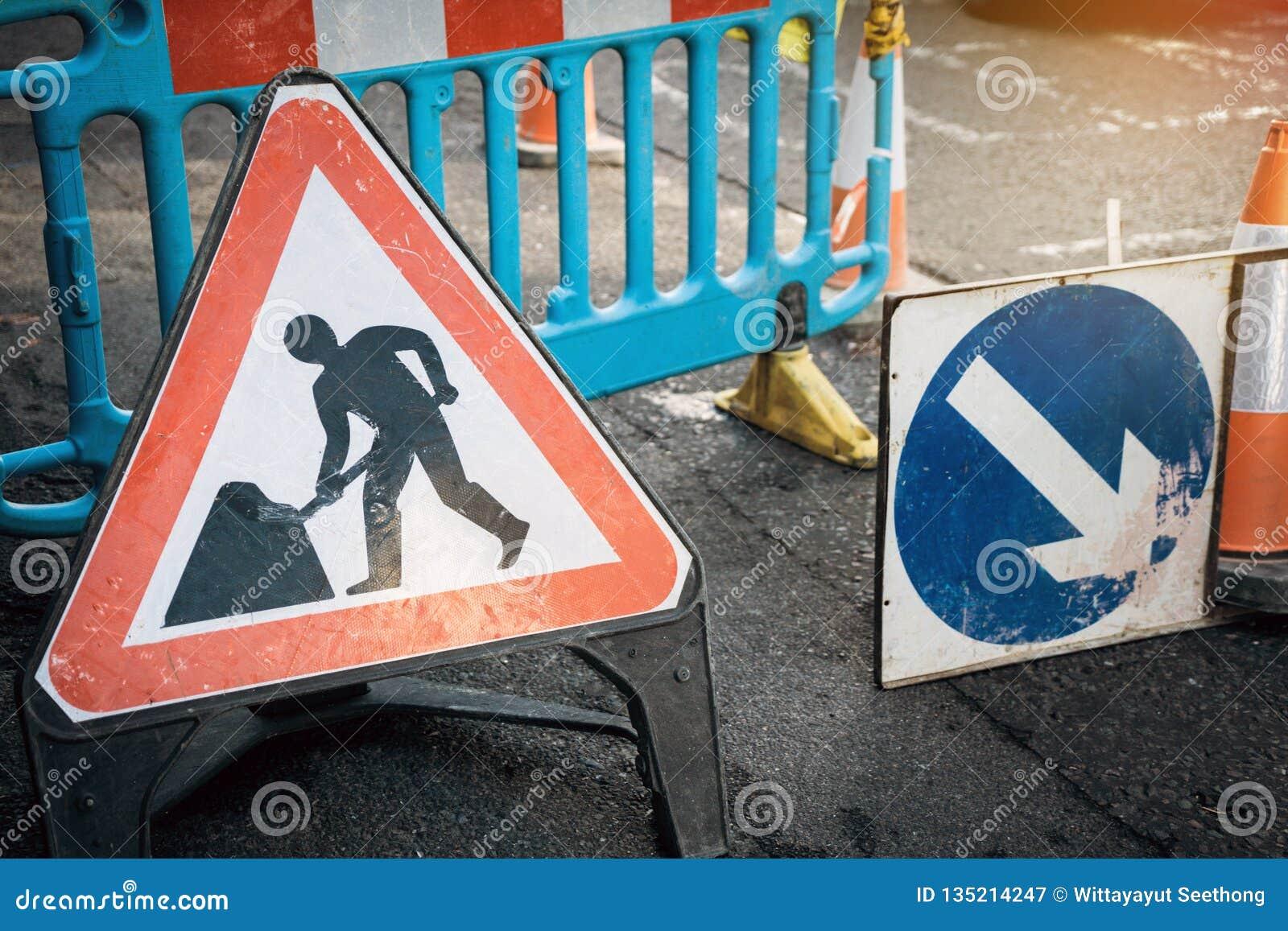 Im Bau Brettzeichen auf der geschlossenen Straße mit Pfeilzeichen und Verkehrskegel