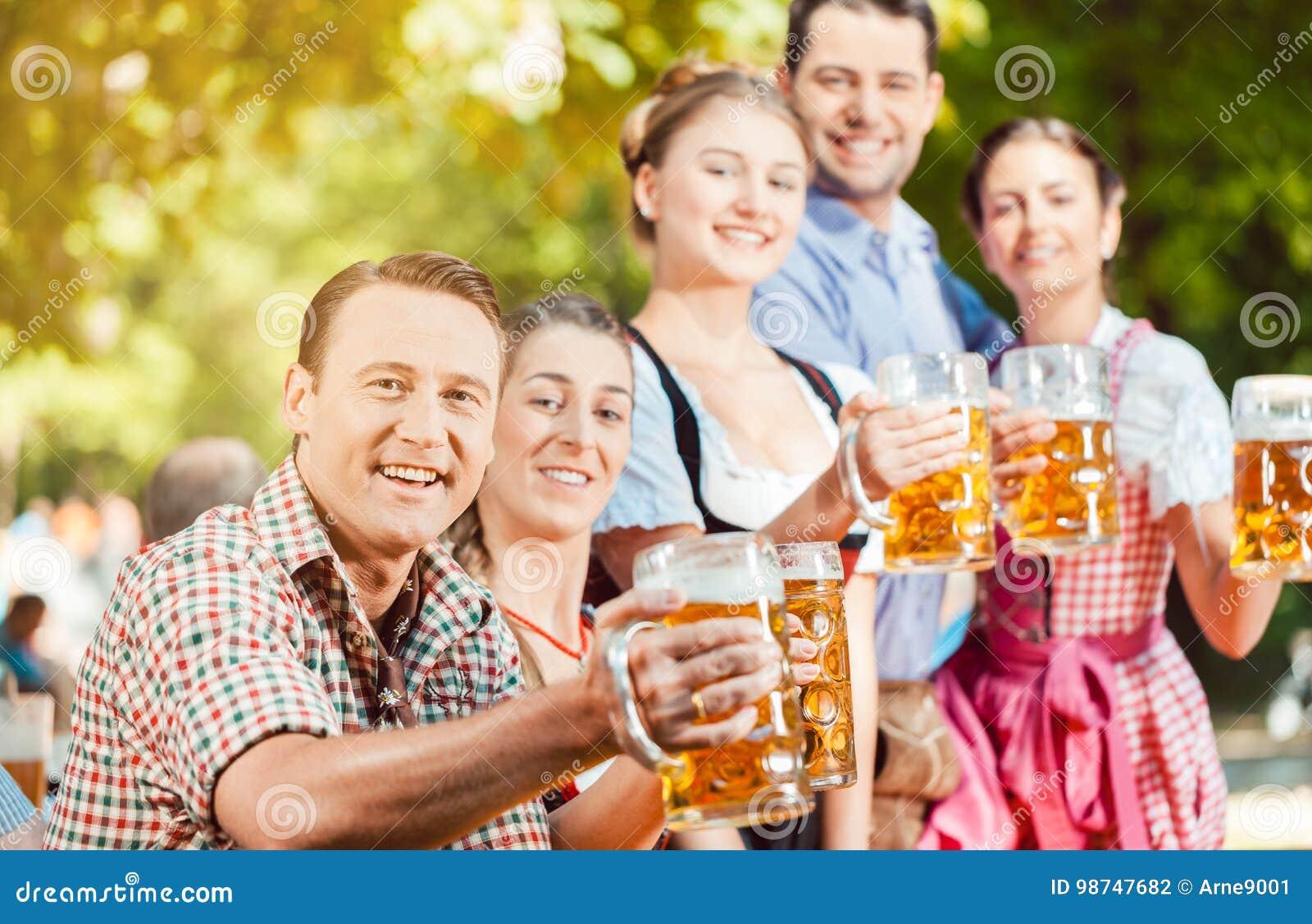 Im Biergarten - Freunde, die Bier im Bayern auf Oktoberfest trinken