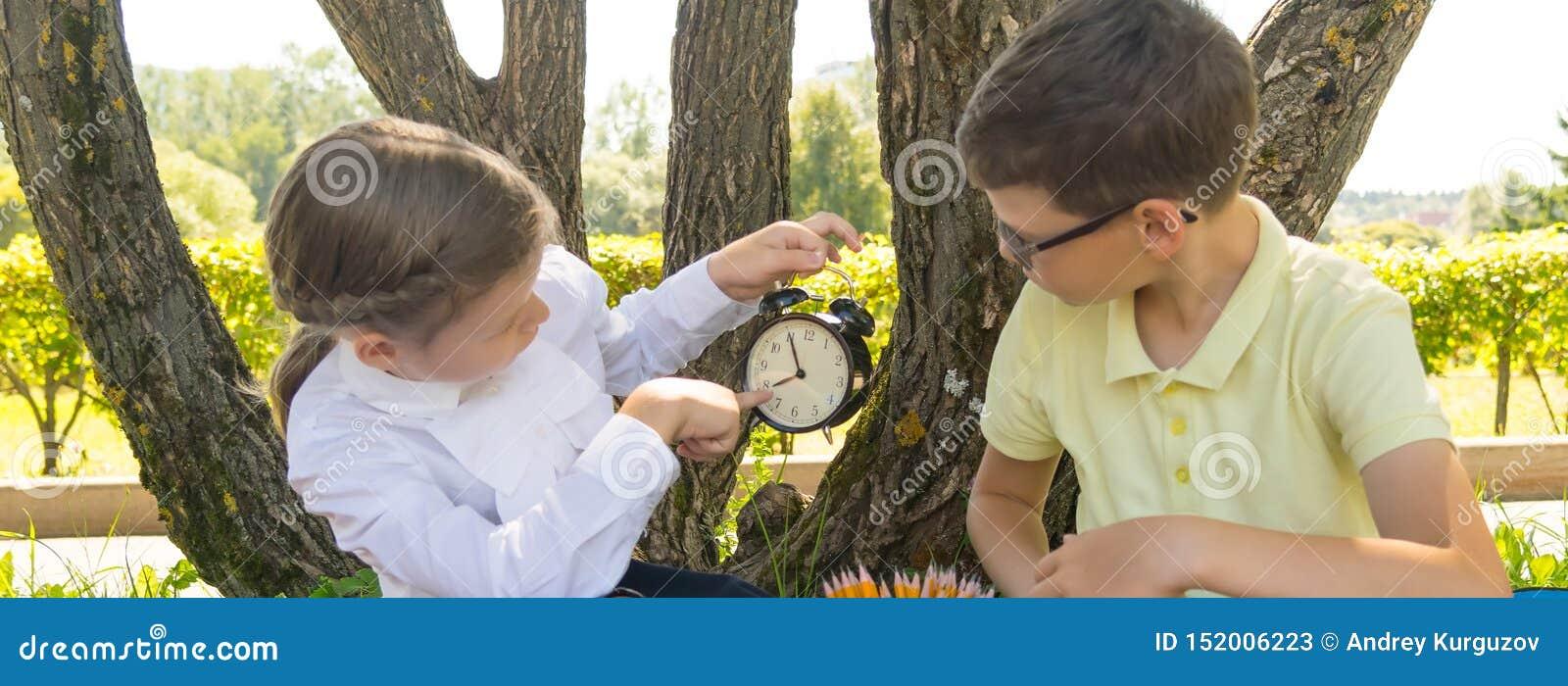 Im Park in der Frischluft, zeigt das Mädchen die Jungenzeit auf der Uhr damit, für die Lektion spät nicht zu sein