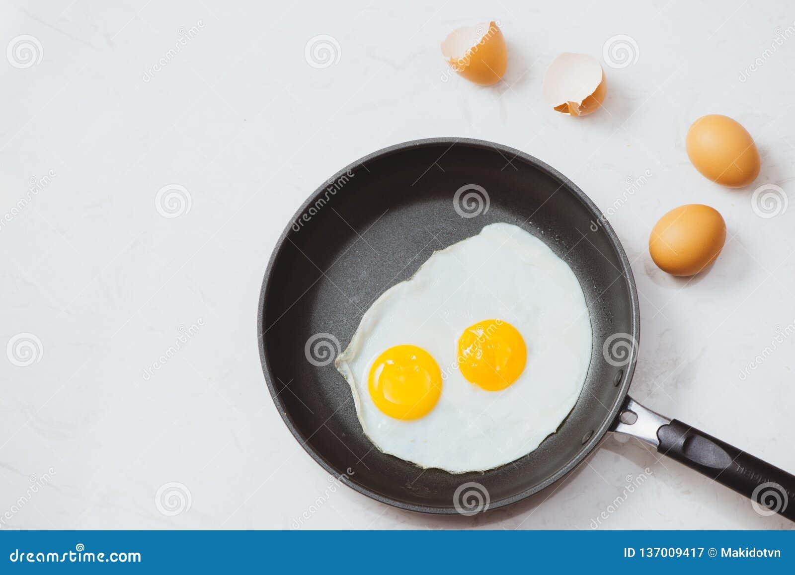 Im Prozess essen, Spiegeleier in einer Bratpfanne zum Frühstück auf einem weißen Hintergrund Tageslicht
