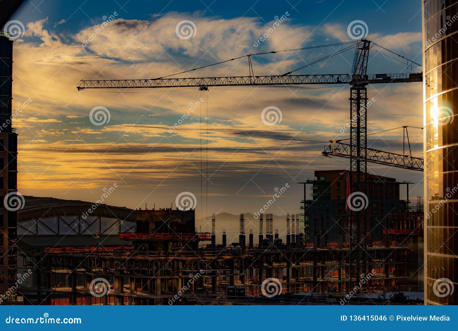 Im Stadtzentrum gelegener Sonnenuntergang über Baustelle mit Kran