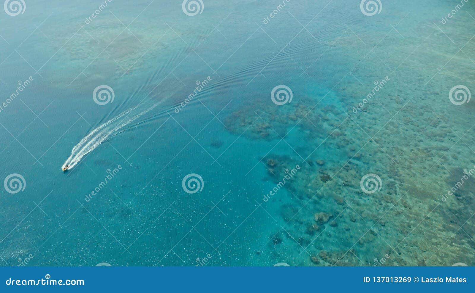 Image aérienne de bourdon de stupéfaction d un petit bateau de pêche écrivant un ancrage d océan de mer d a dans un canal à côté