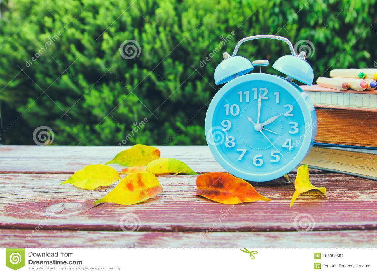 Image of autumn Time Change. Fall back concept. Dry leaves and vintage alarm Clock
