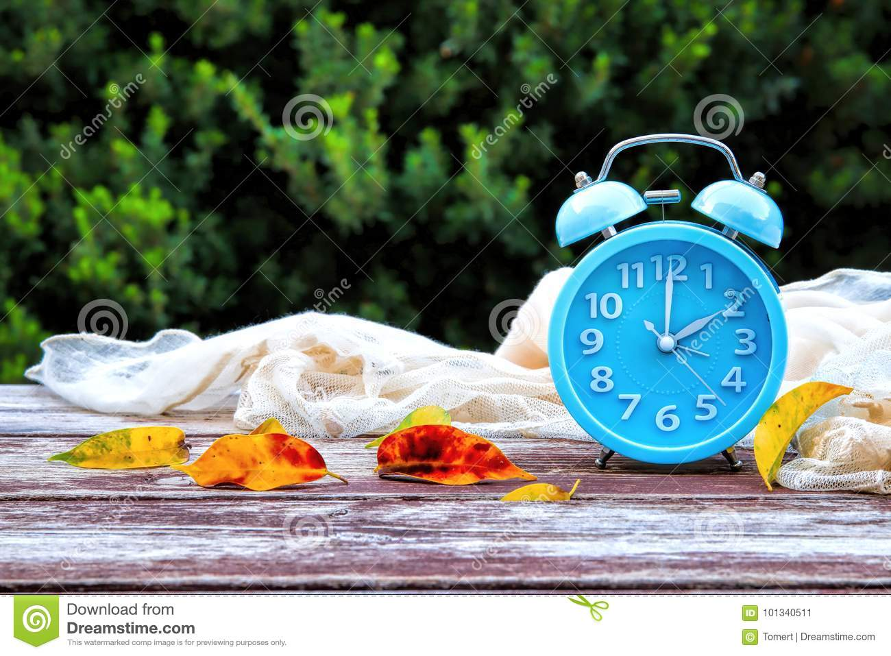 Image of autumn Time Change. Fall back concept. Dry leaves and vintage alarm Clock on wooden table