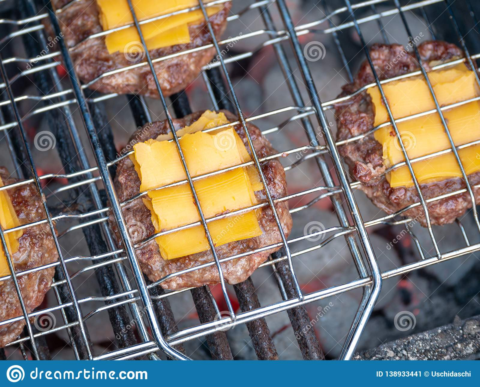Image of bbq burger patties with cheese on grill