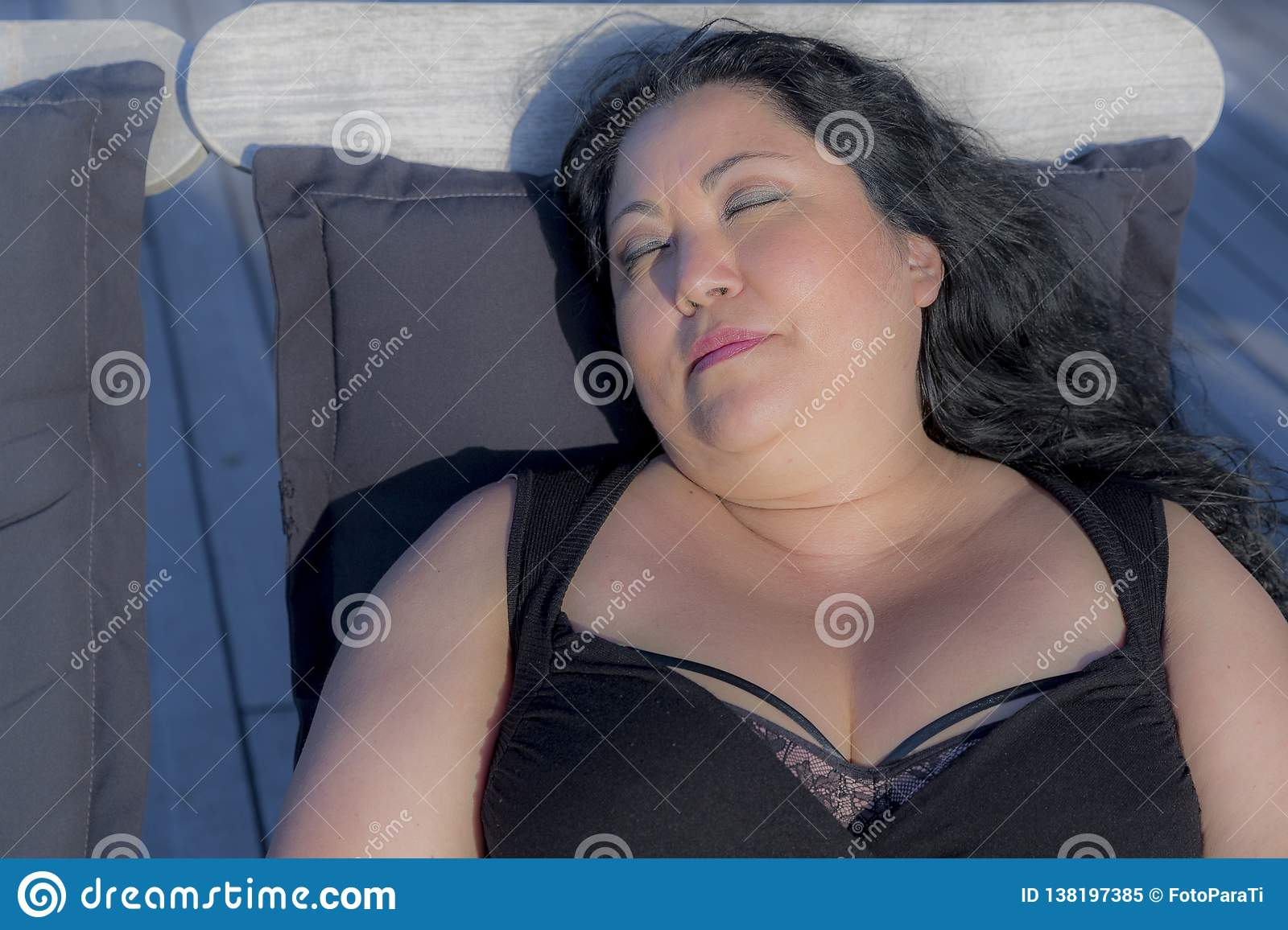 Image of a beautiful relaxed woman sleeping on a sunbathing chair