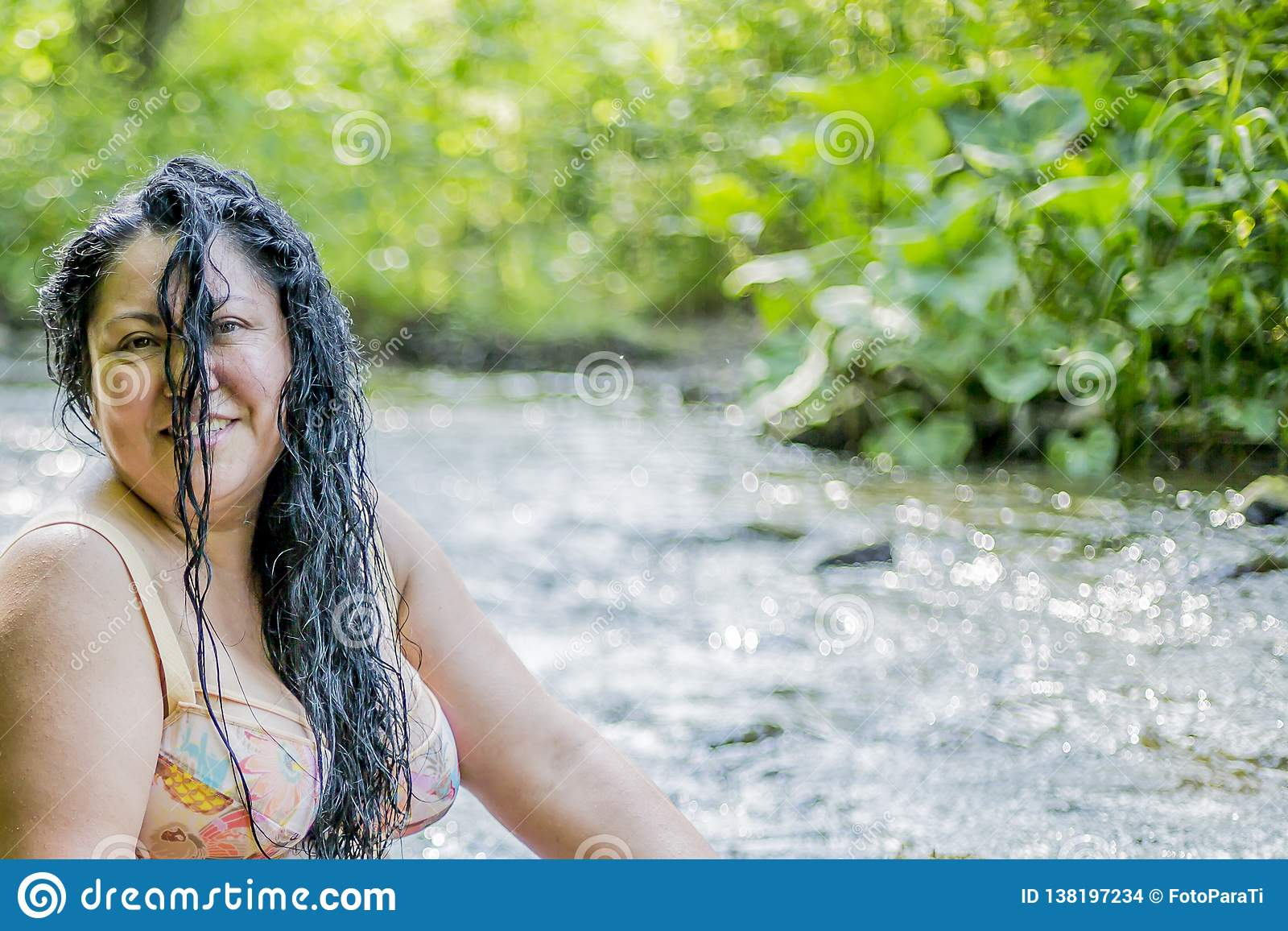 Image of a beautiful woman with long black hair on her face enjoying a wonderful and sunny summer