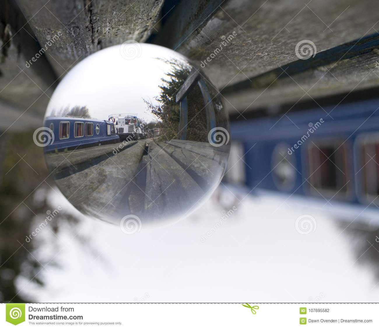 Image of boats moored along canal refracted through glass ball