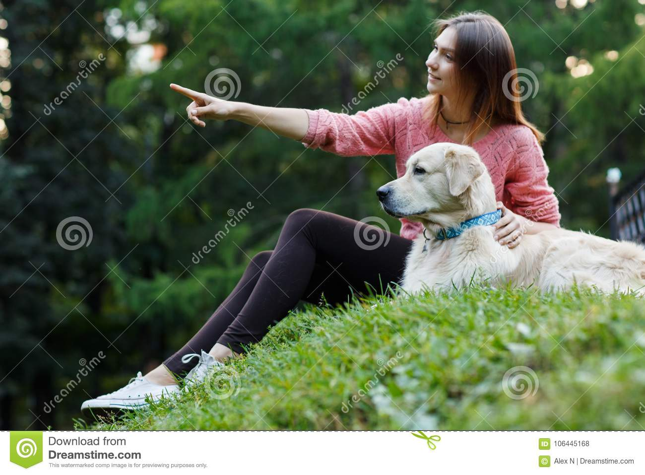 Image from bottom of girl pointing forward next to dog on green lawn