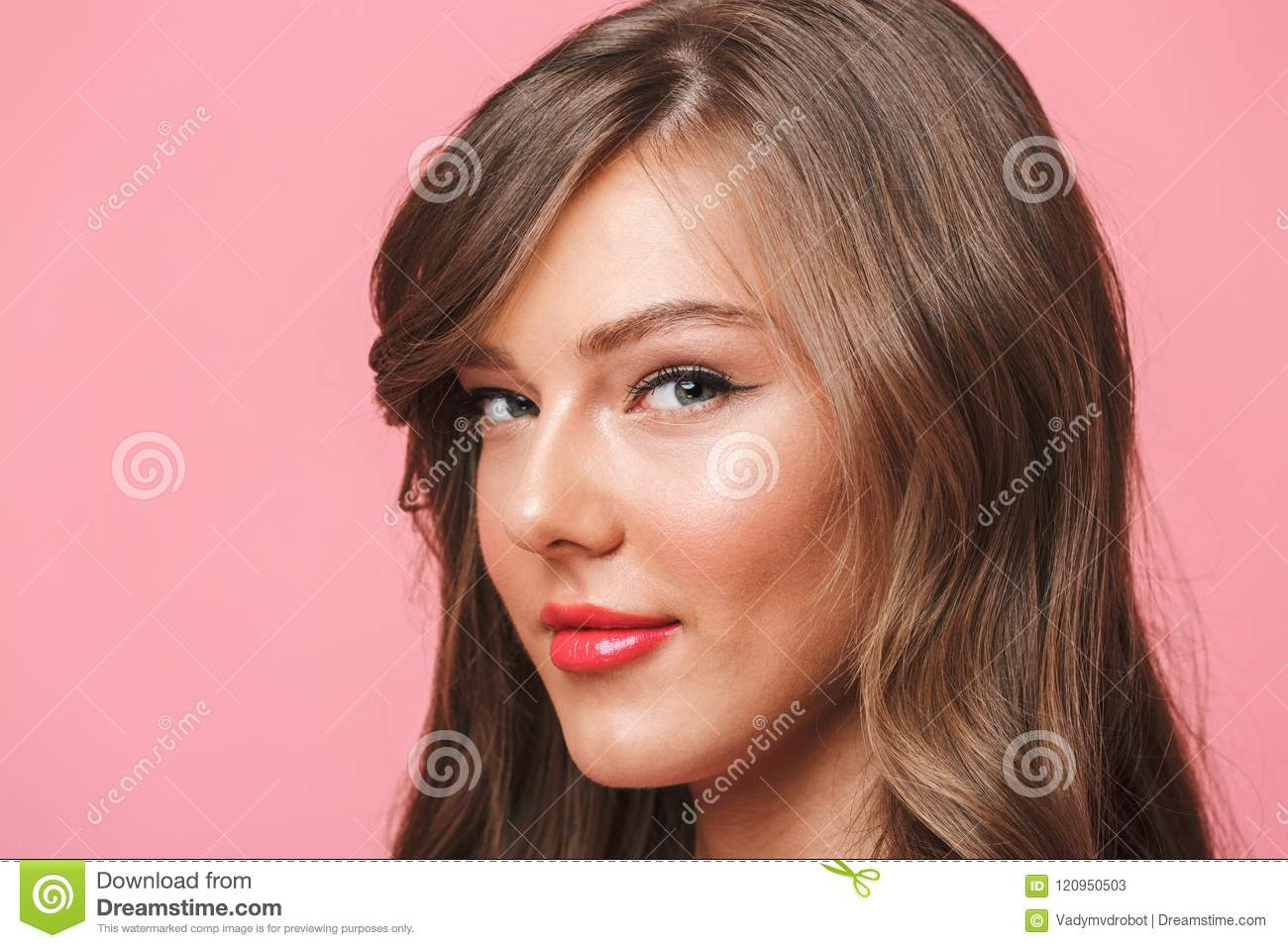 Image closeup of young european woman 20s with long curly hairstyle and evening makeup smiling at camera with seductive look isolated over pink background