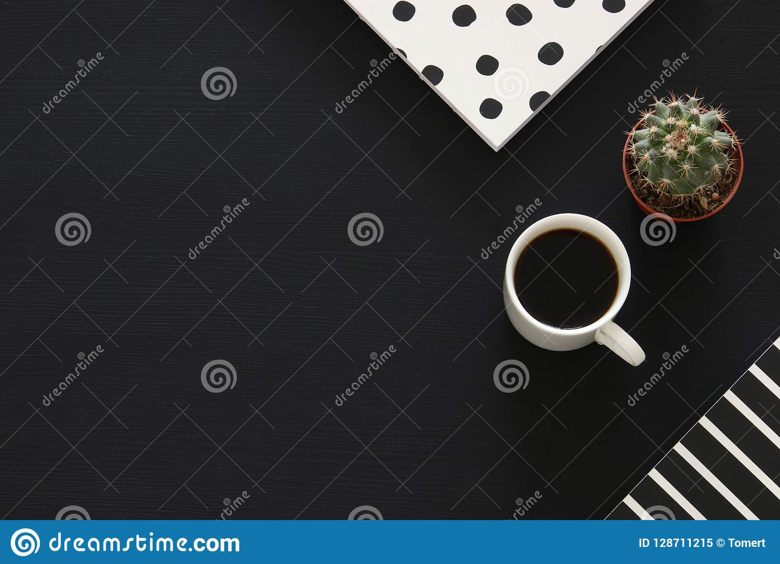 image of coffee cup and notebook over black background. Top view.