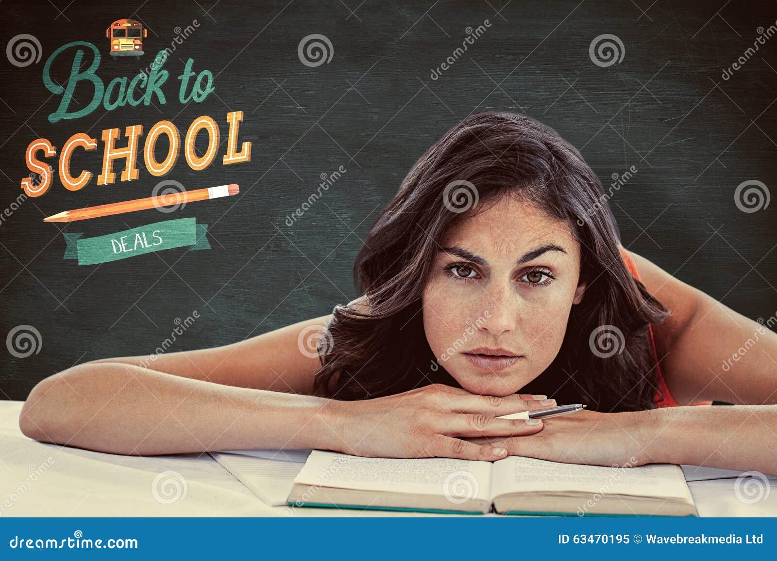 Image composée de chef de froncement de sourcils d étudiant sur ses livres
