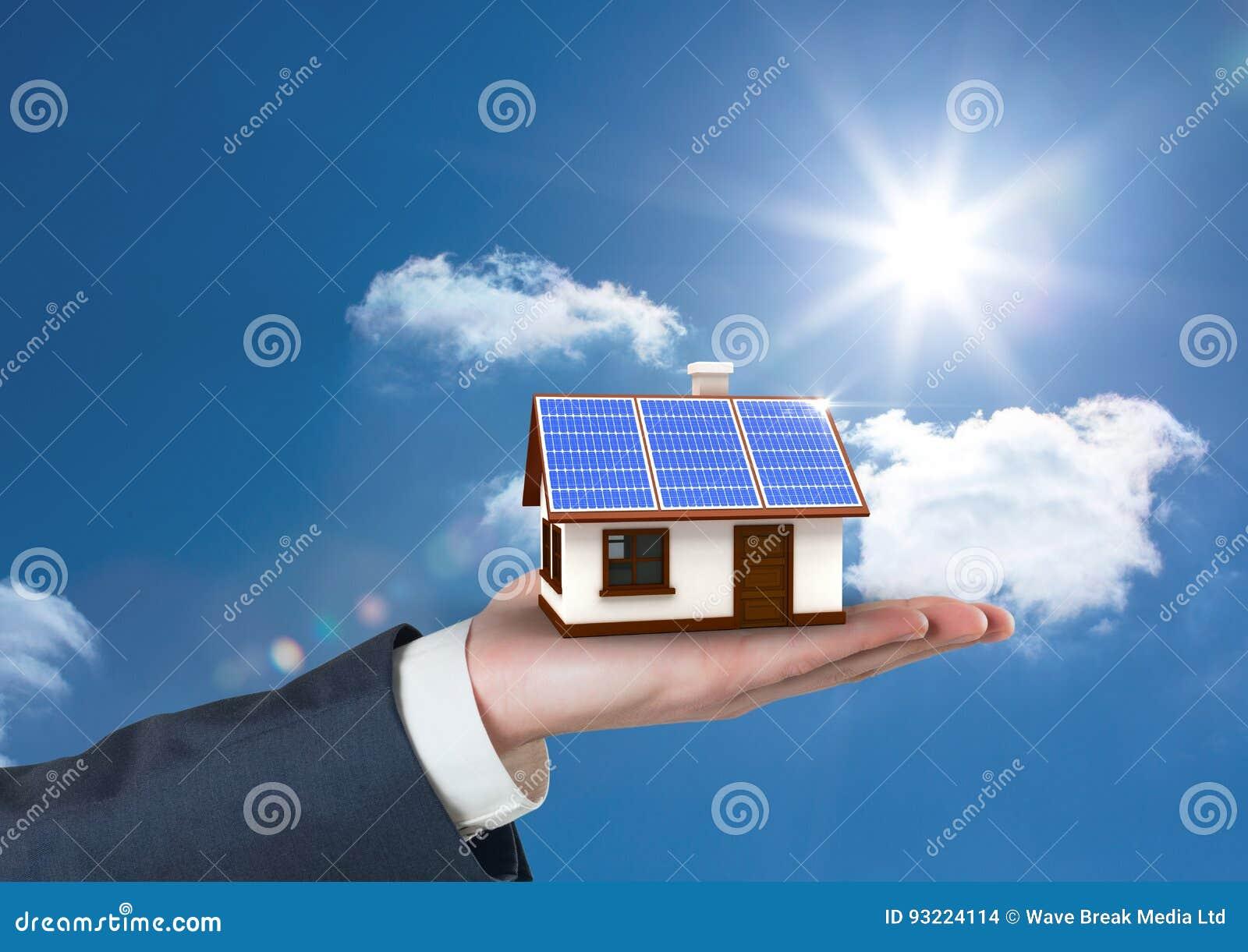 Image composée de Digital de la main cultivée tenant la maison avec le toit du panneau solaire contre le ciel