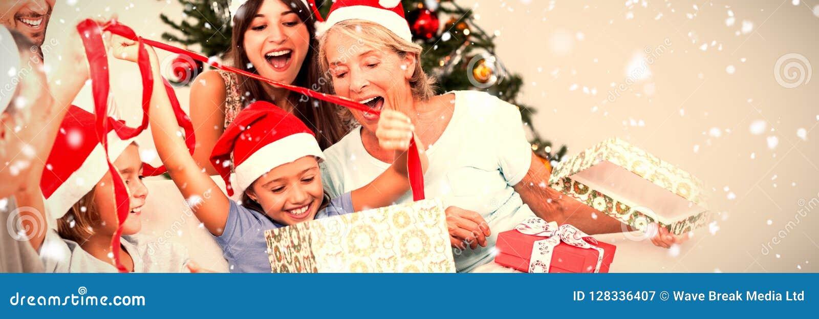 Image composée de famille heureuse aux cadeaux d ouverture de Noël ensemble