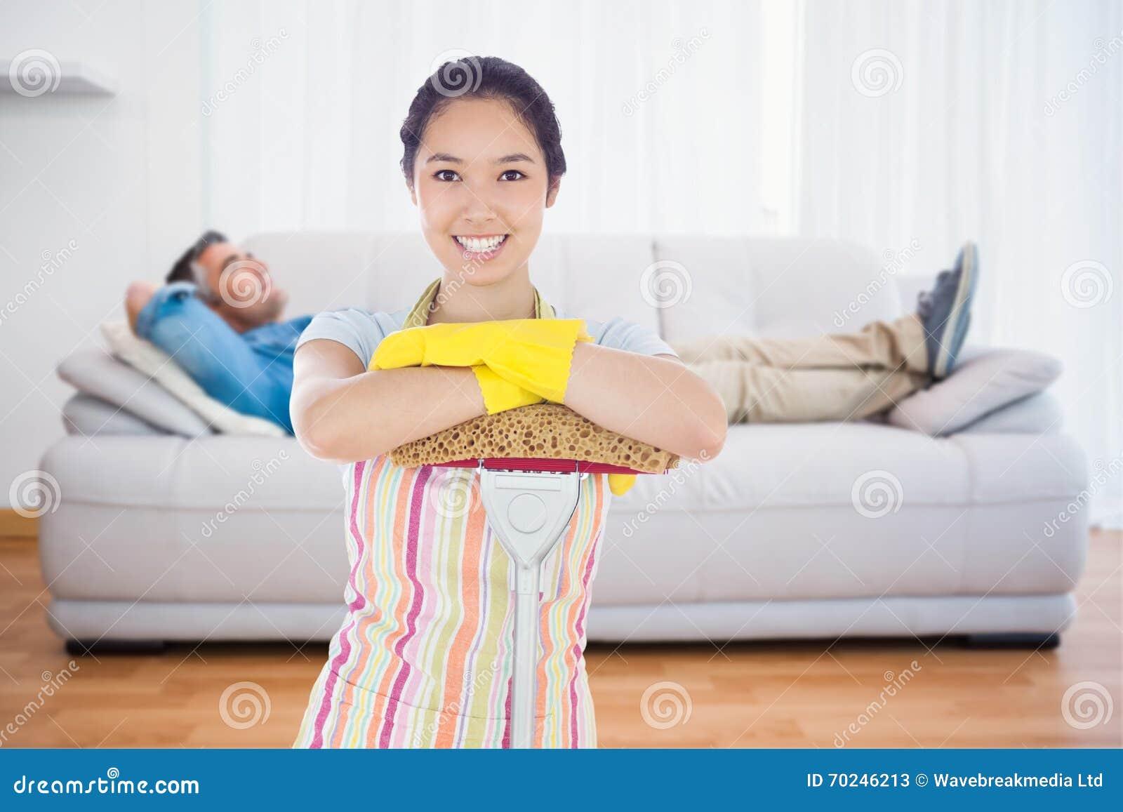 Image composée de femme de sourire se penchant sur le balai